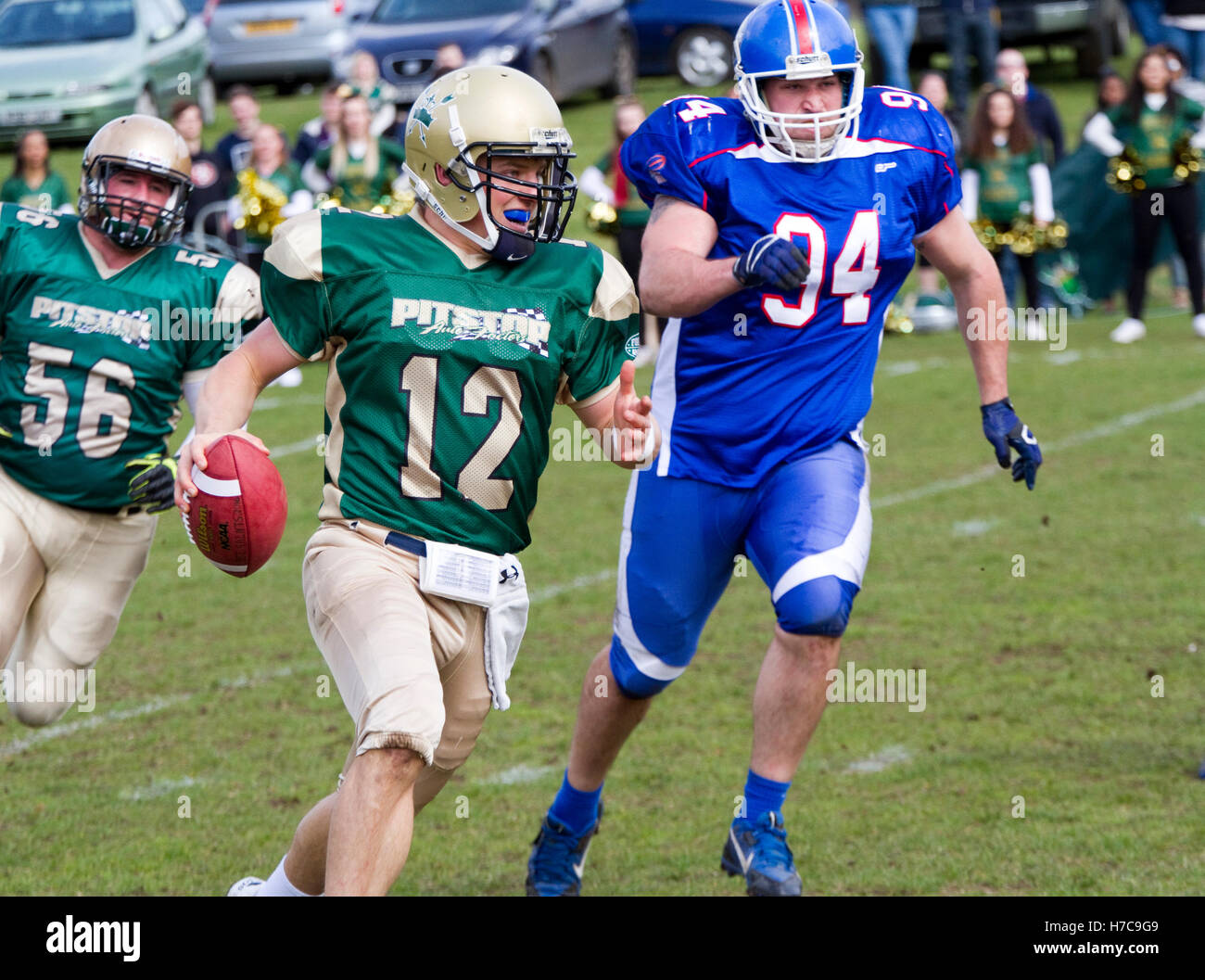 Quarterback with the ball pursued by large opponent - Stock Image