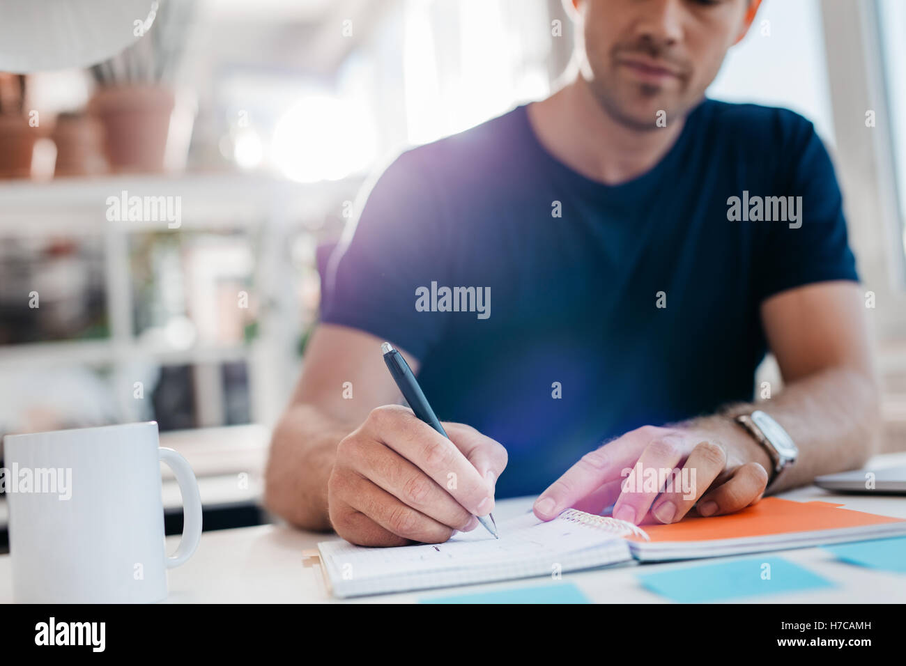 Young businessman writing down important notes in diary at his desk. Young businessman writing in his notepad. - Stock Image