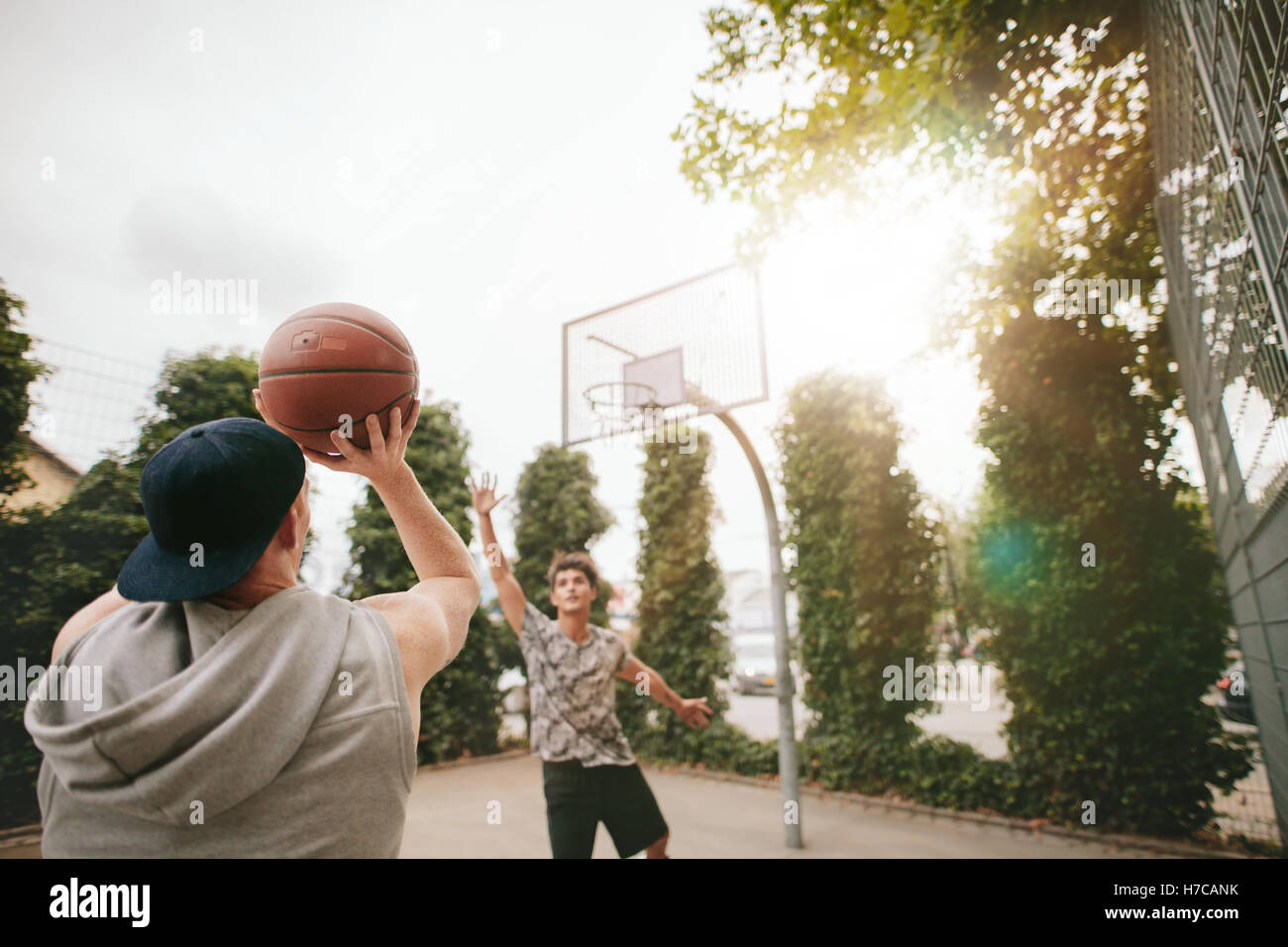 Streetball players on court playing basketball. Young guy taking shot to the basket with friend blocking. - Stock Image