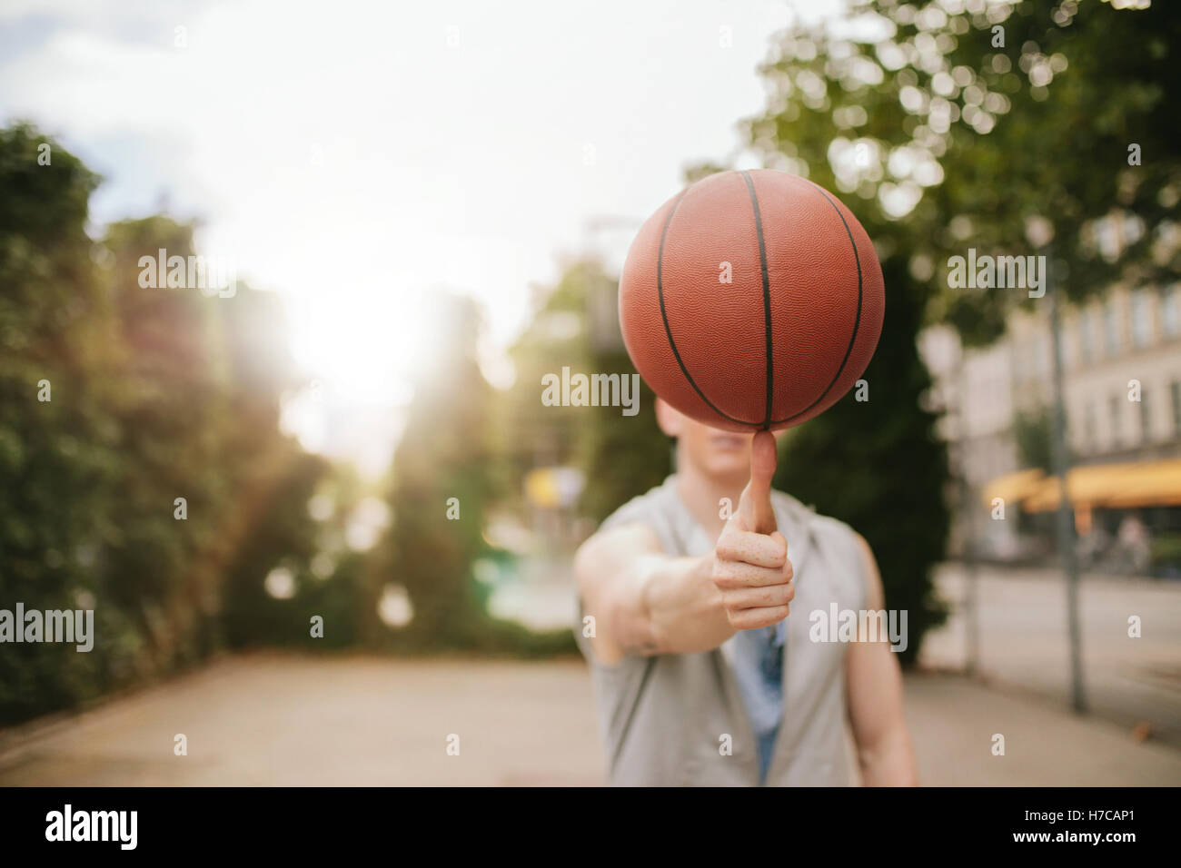 Man balancing basketball on his thumb on outdoor court. Streetball player spinning the ball. Focus on basketball. - Stock Image