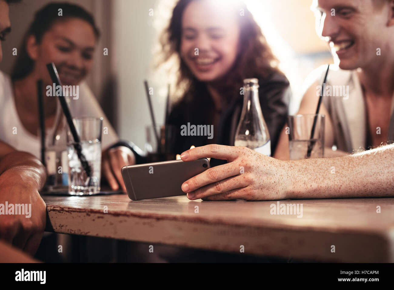 Group of friends sitting in a bar and watching a funny video on mobile phone, focus on mobile phone in man hand. - Stock Image