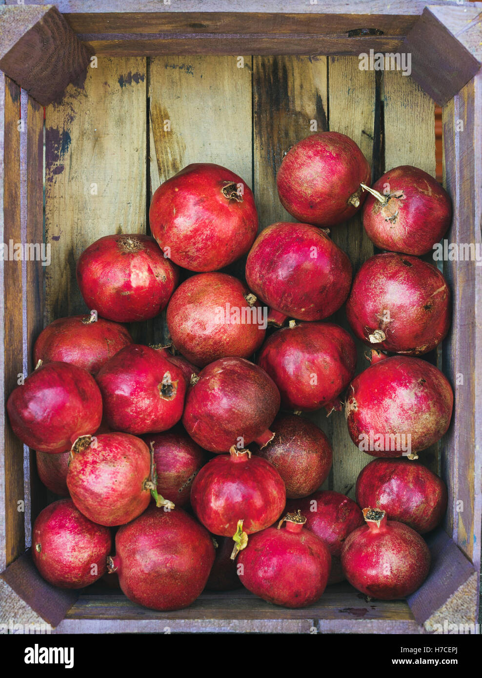 Turkish ripe red pomegranates in rustic wooden box, top view, copy space, vertical composition - Stock Image