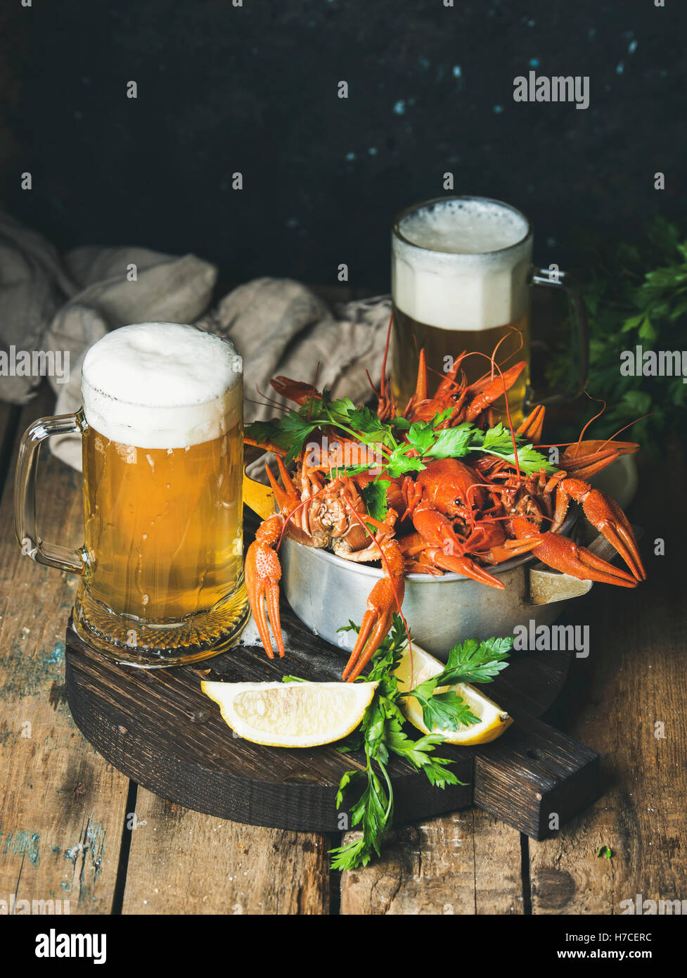 Two pints of wheat beer and boiled crayfish with lemon and parsley on dark round serving board over rustic wooden - Stock Image