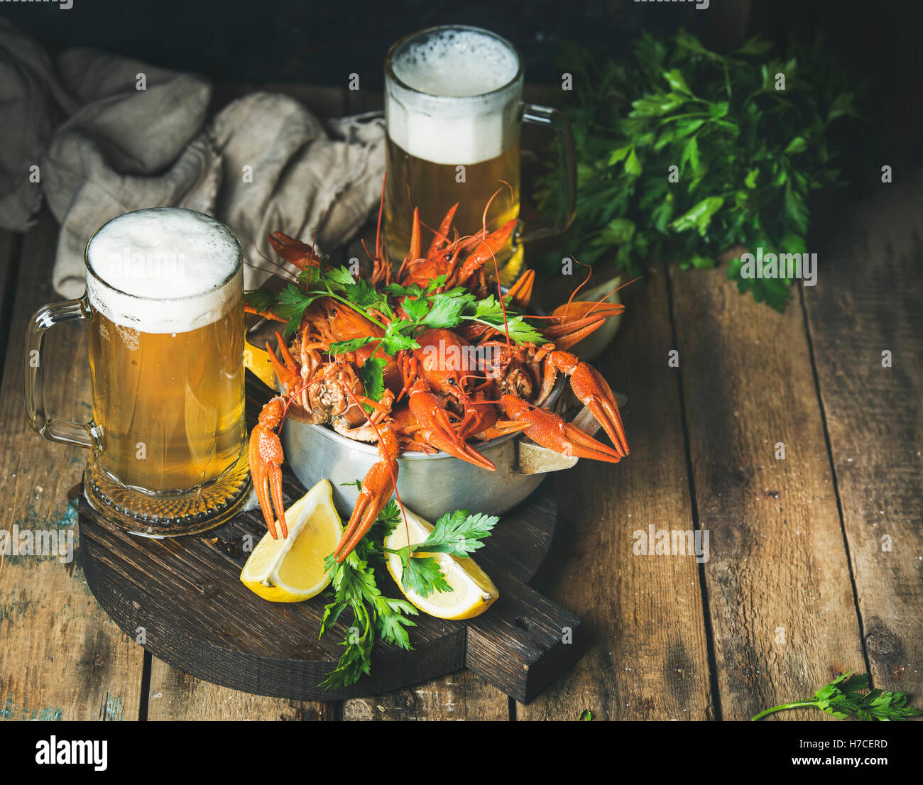 Two pints of wheat beer and boiled crayfish in metal pan served with with lemon and parsley on dark round serving - Stock Image