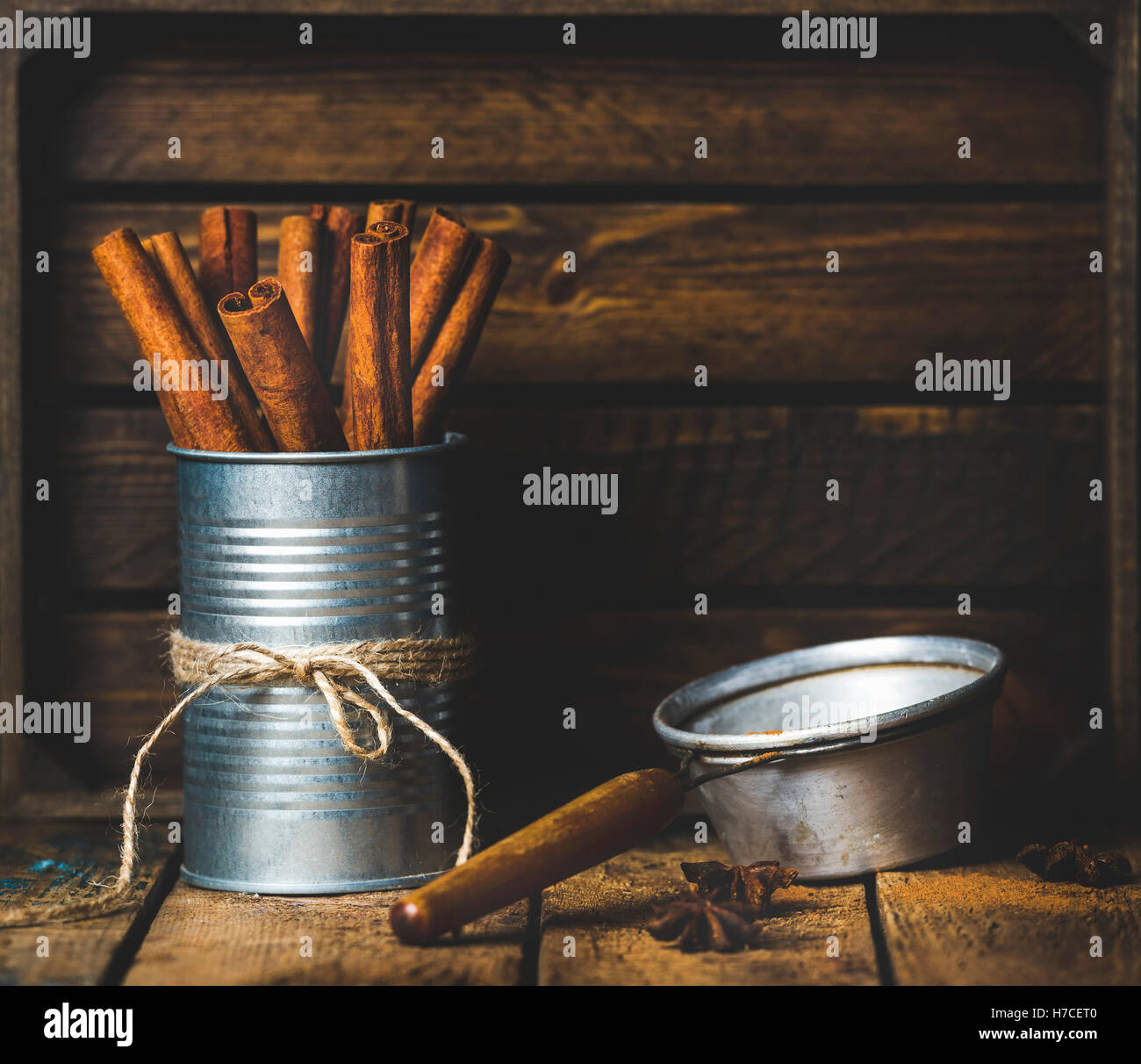 Cinnamon sticks in can tied with rope, anise stars and sieve on rustic wooden background, copy space - Stock Image