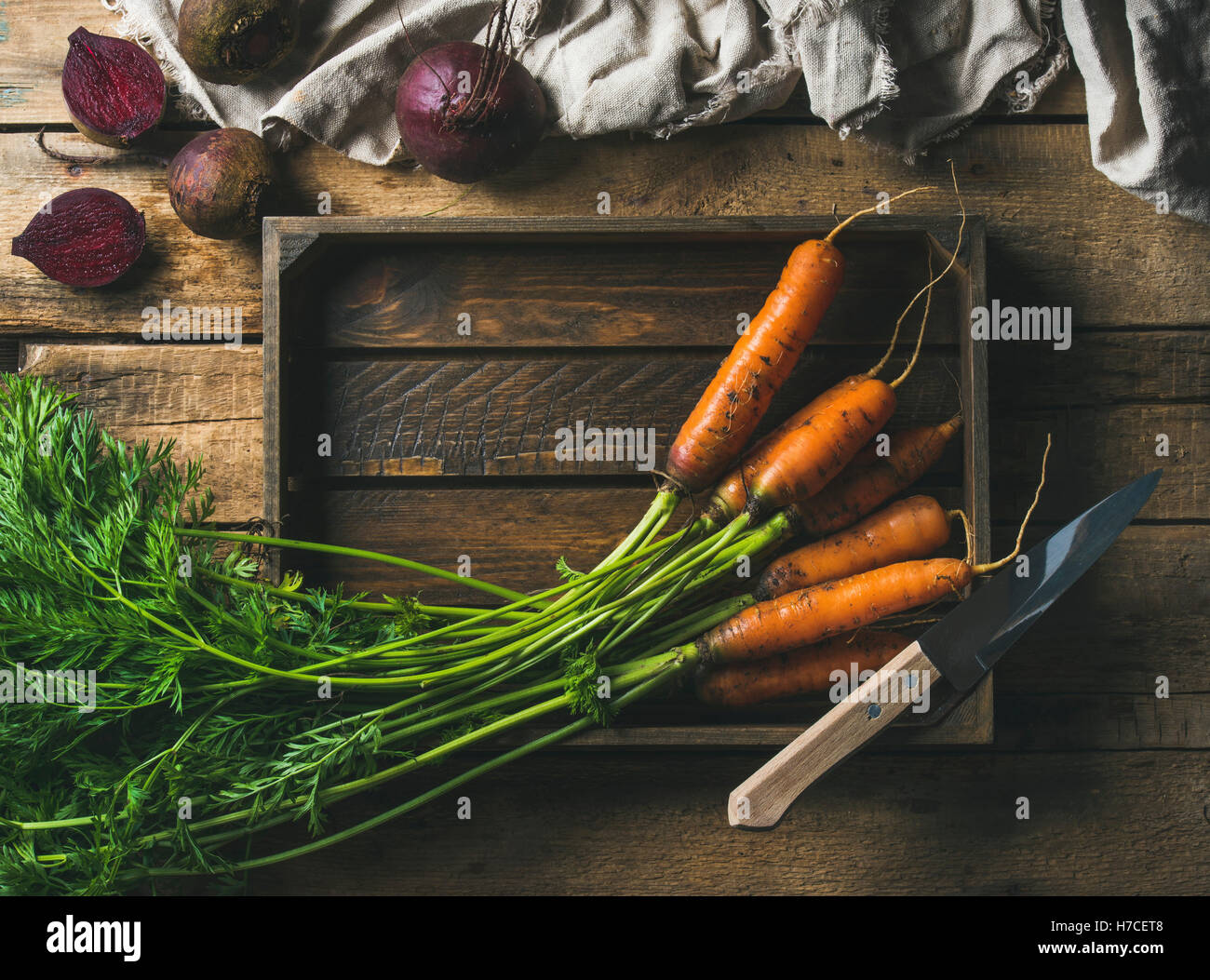 Healthy food cooking background. Vegetable ingredients. Fresh garden carrots and beetroots in wooden tray over rustic - Stock Image