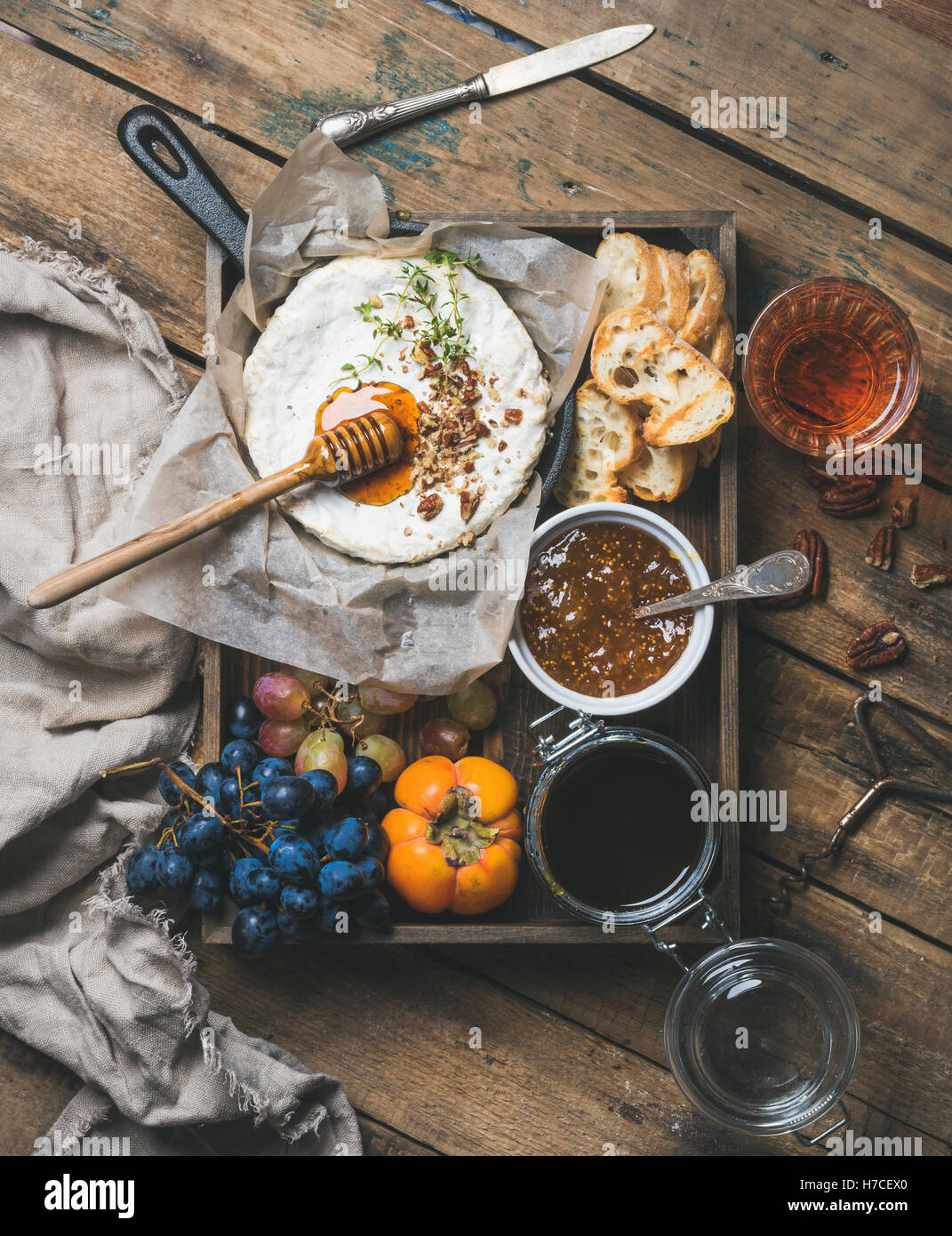 Cheese, fruit and wine set. Camembert in small pan with honey, nuts and herbs, grapes, persimmon, fig jam, baguette - Stock Image