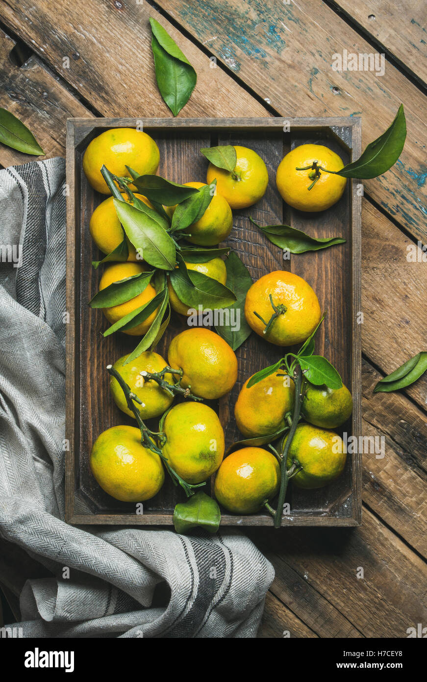 Fresh picked Mediterranean tangerines with green leaves in crate over rustic wooden background, top view, vertical - Stock Image