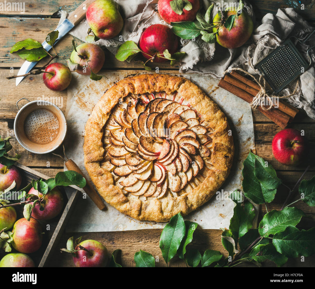 Apple crostata pie with cinnamon served with fresh garden apples with leaves on rustic wooden background, top view, Stock Photo