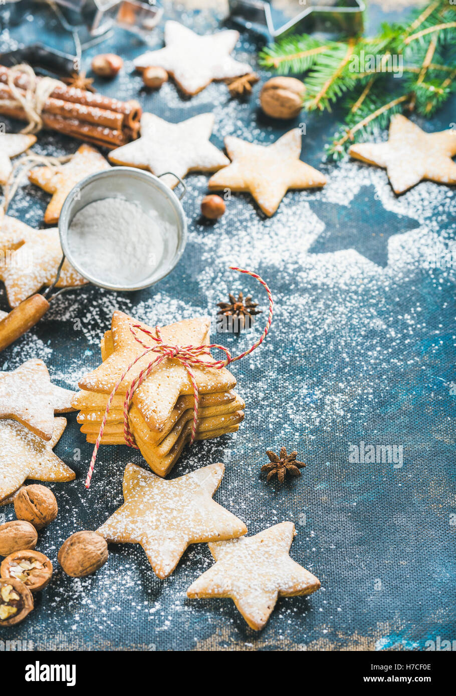 Gingerbread Christmas star shaped cookies with cinnamon, anise and nuts served with fir-tree branch on dark plywood - Stock Image