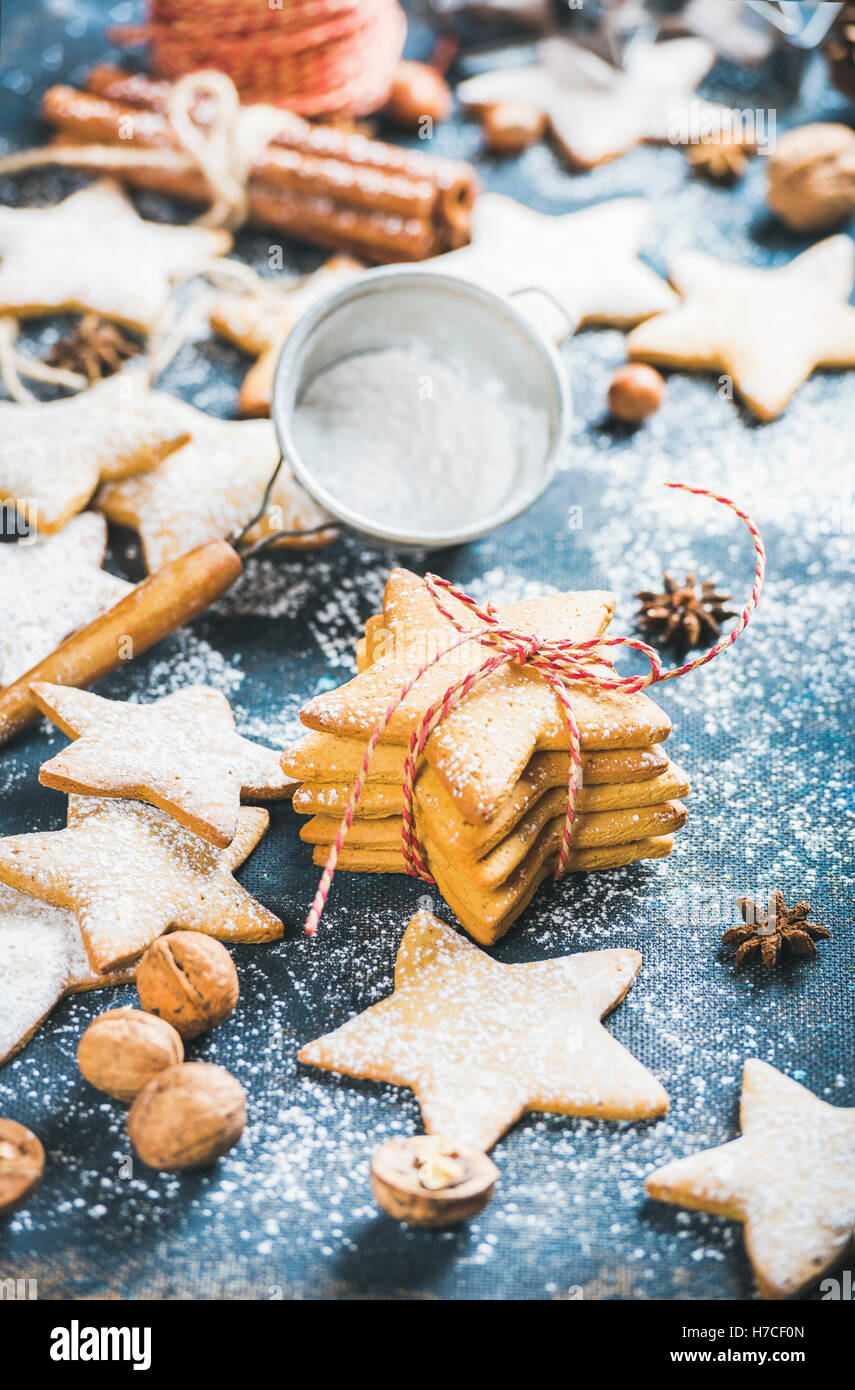 Homemade gingerbread star shaped cookies with cinnamon, anise and nuts on dark blue painted plywood background, - Stock Image