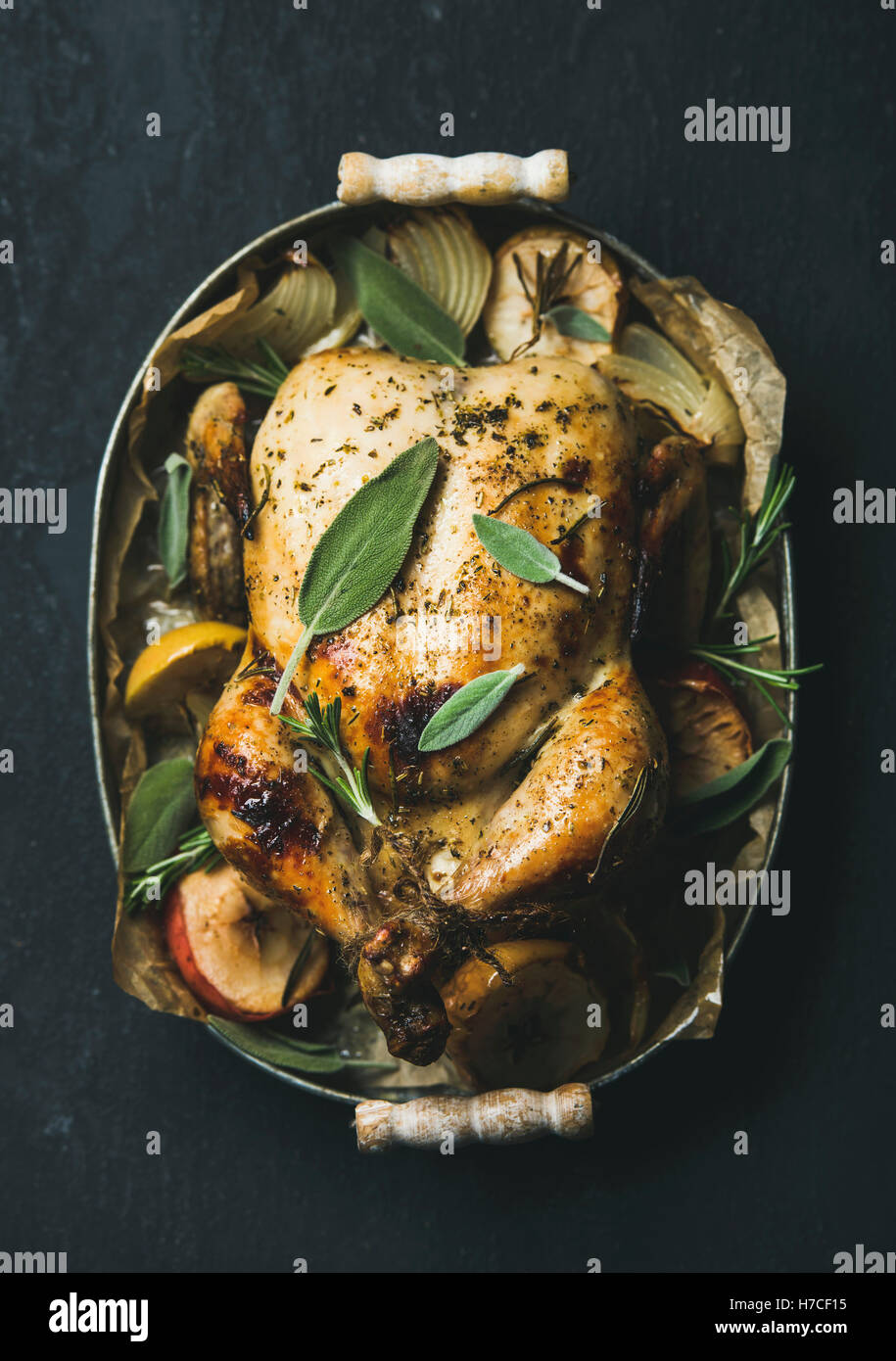 Oven roasted whole chicken with onion, apples and sage in metal serving tray over dark stone background, top view. - Stock Image