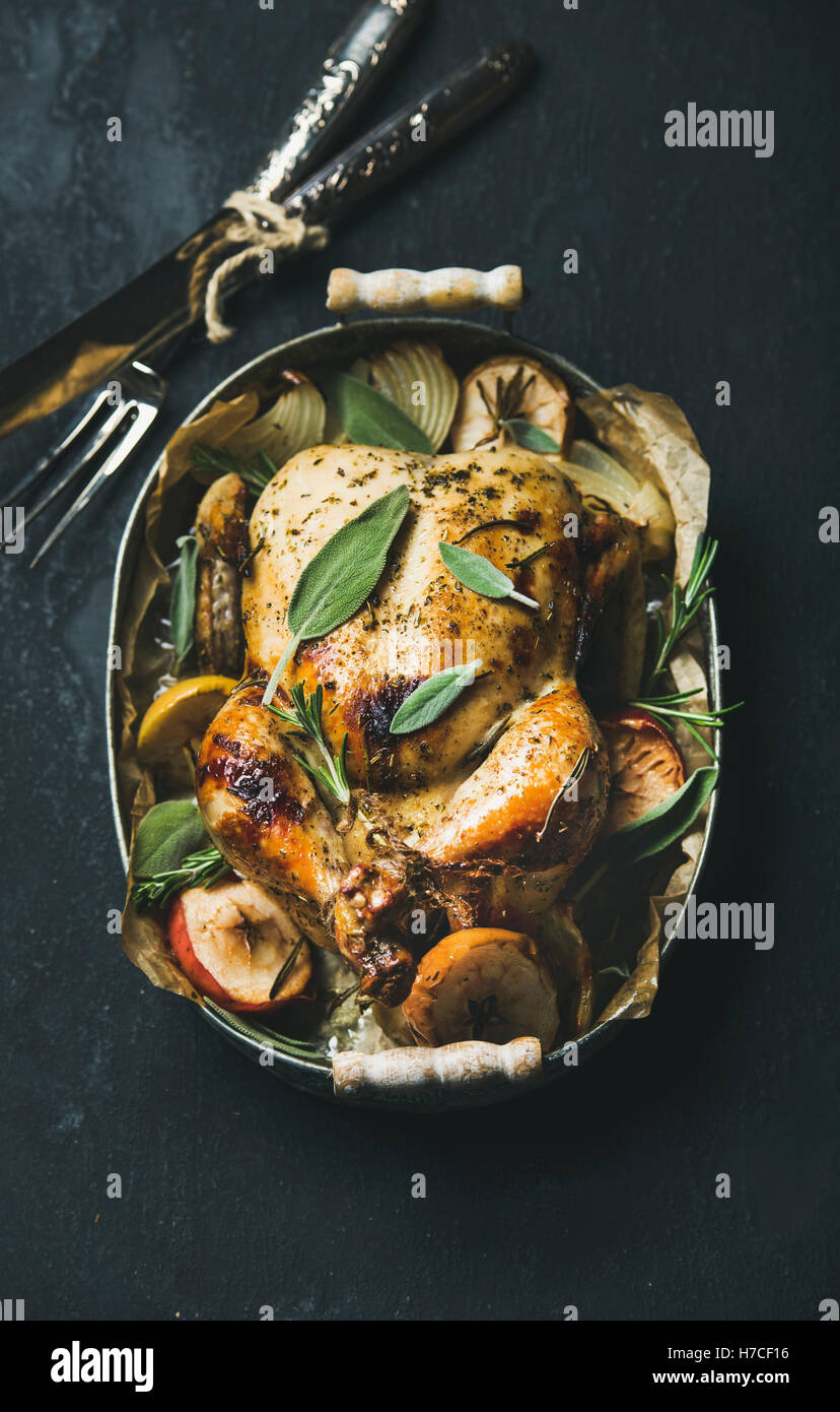 Oven roasted whole chicken with onion, apples and sage in serving tray with cutlery over dark stone background, - Stock Image
