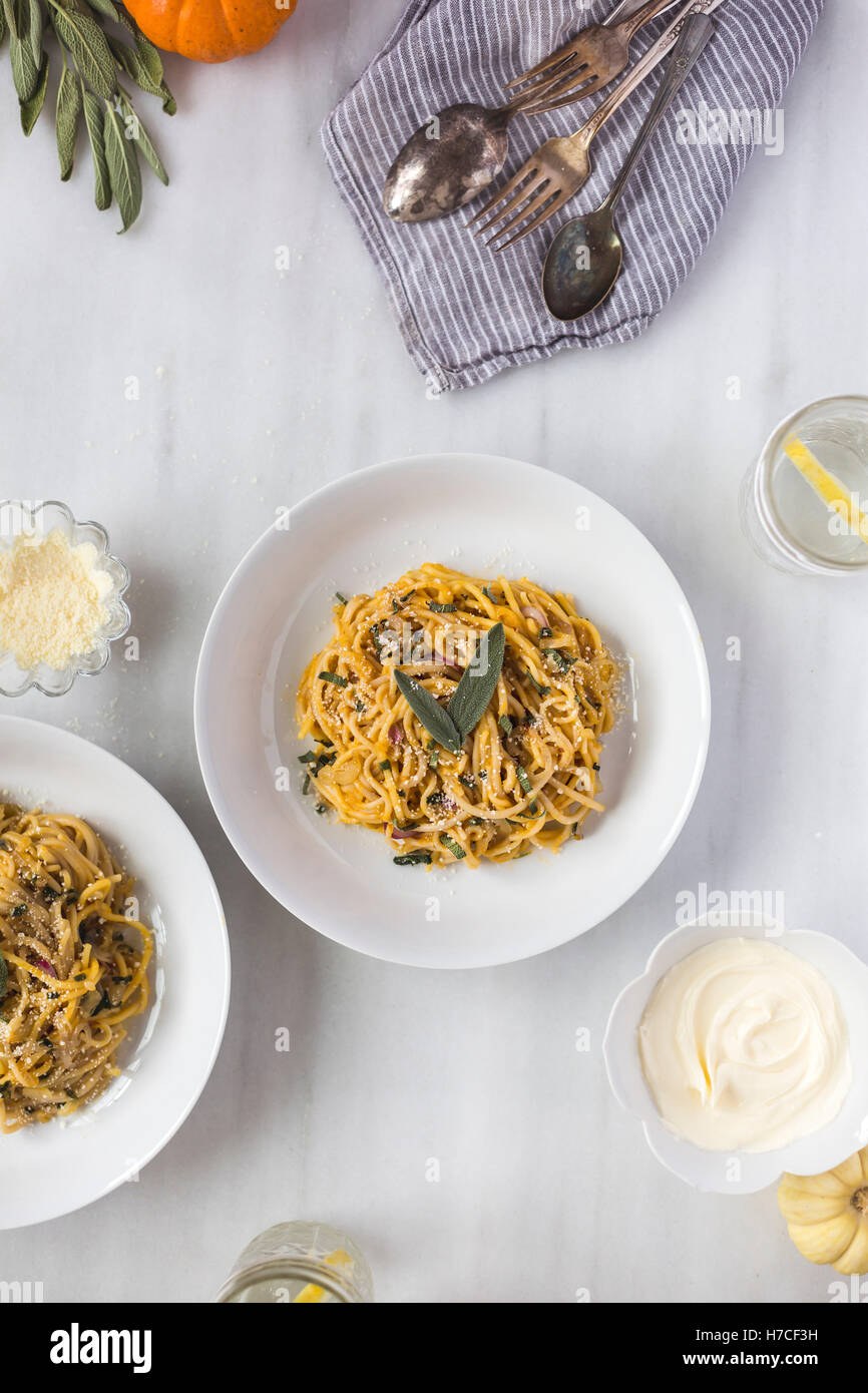 Two bowls of Pumpkin Creme Fraiche Pasta with Sage accompanied with a bowl of creme fraiche are photographed from - Stock Image