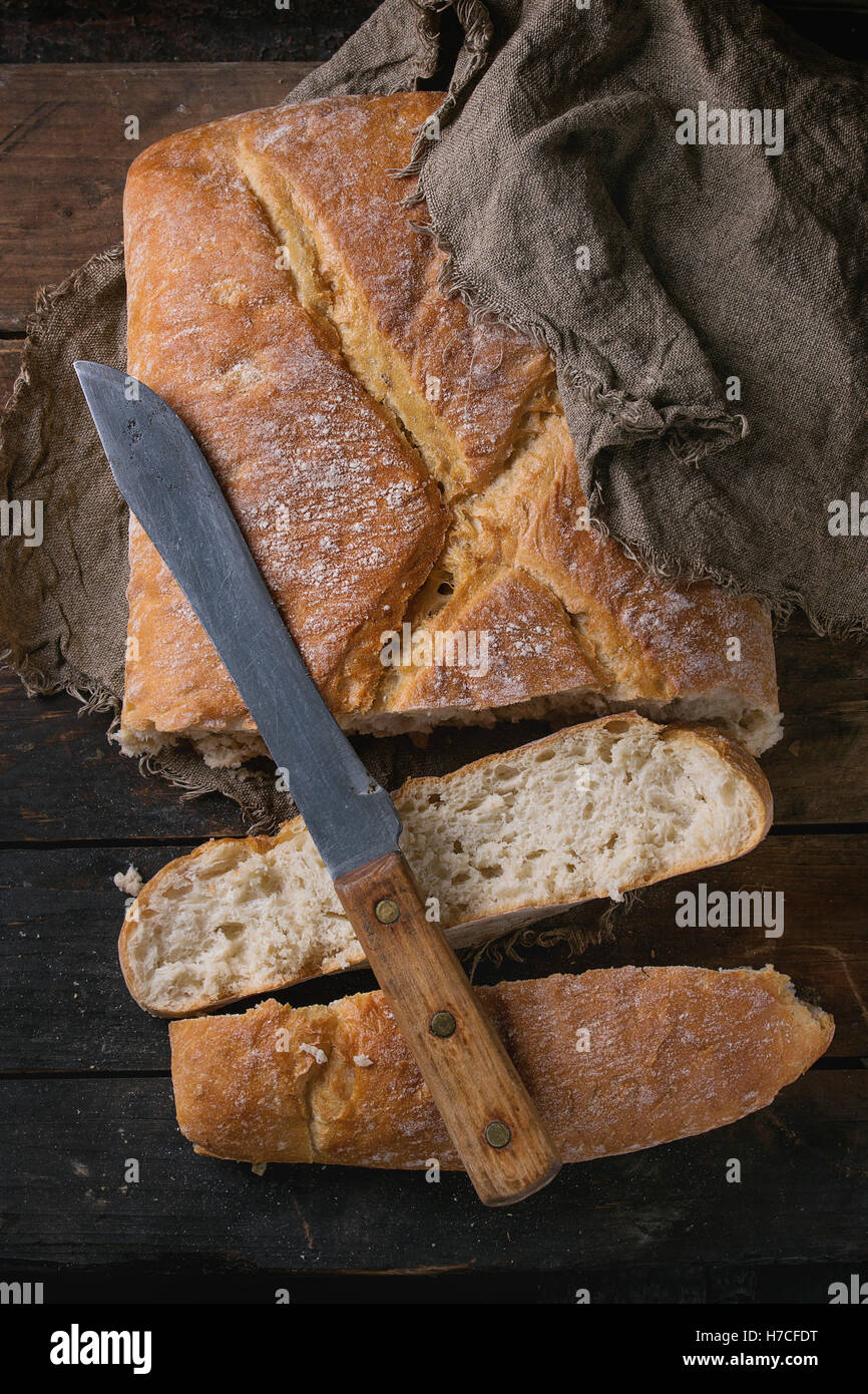 Fresh slice artisan bread under sackcloth with vintage knife over old wooden background. Overhead view. - Stock Image