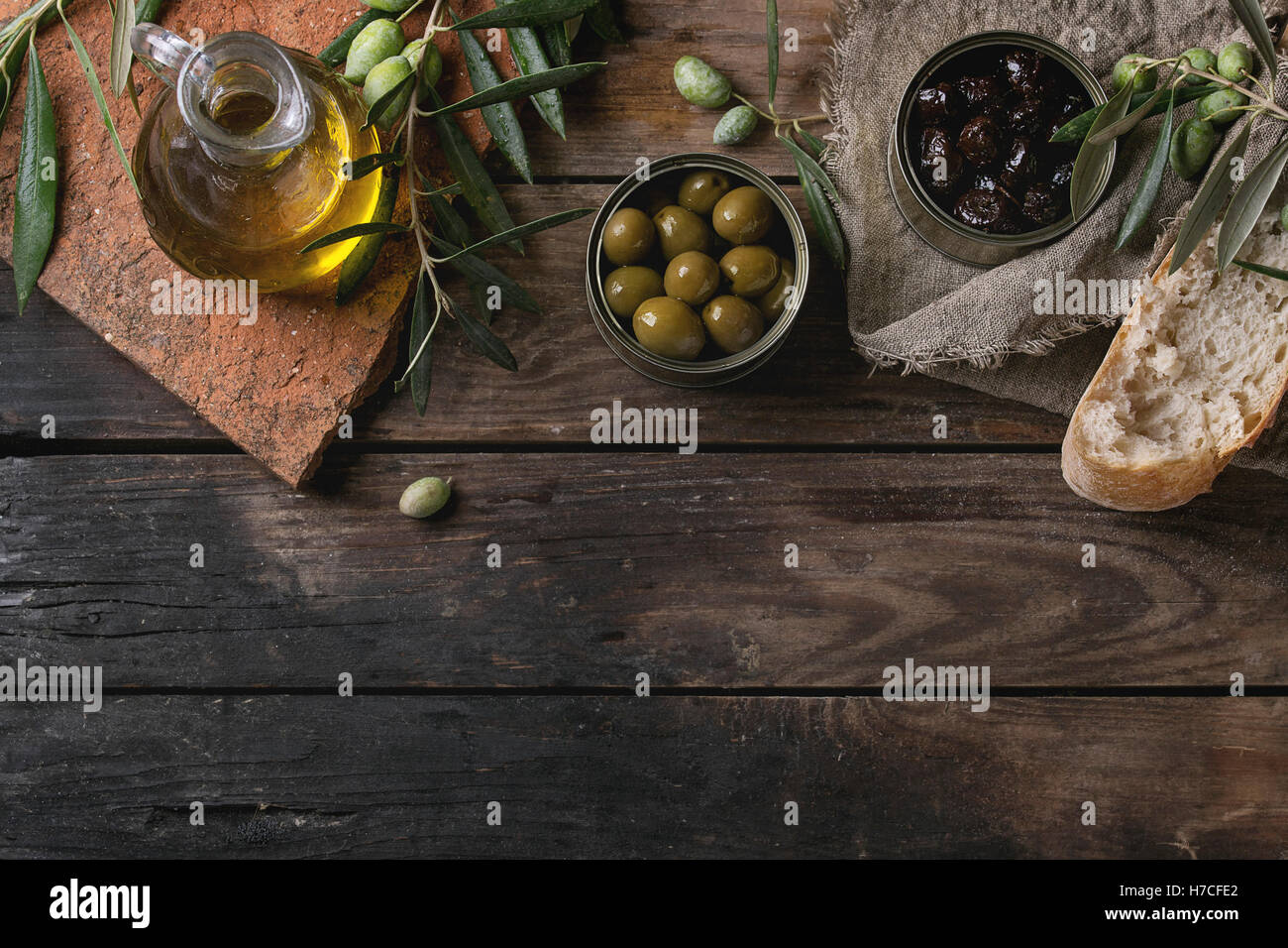 Green and black olives in tin cans with loaf of fresh bread and young olives branch on sackcloth, bottle of olive - Stock Image