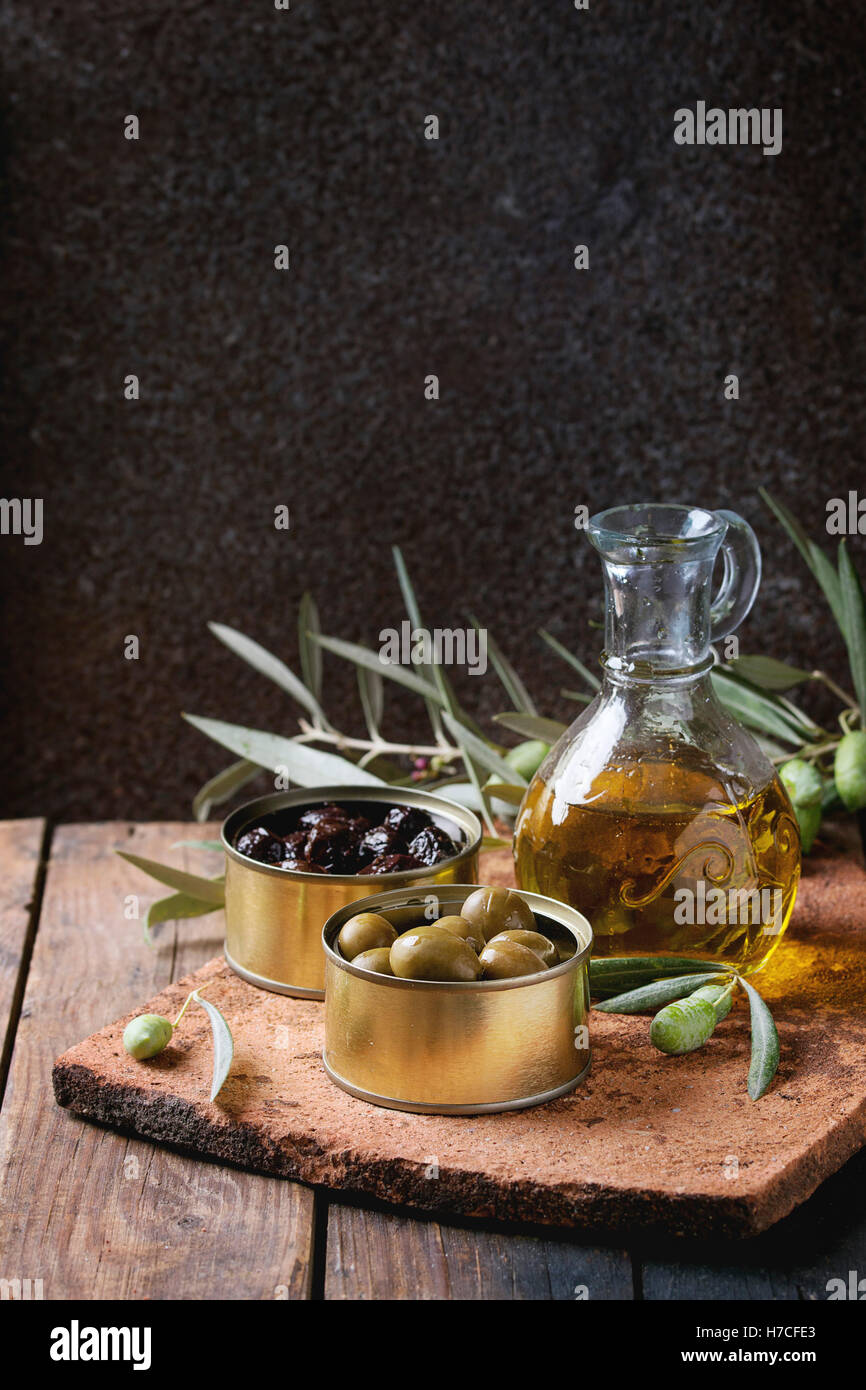 Green and black olives in tin cans, young olives branch and bottle of olive oil on clay board over old wood background. - Stock Image