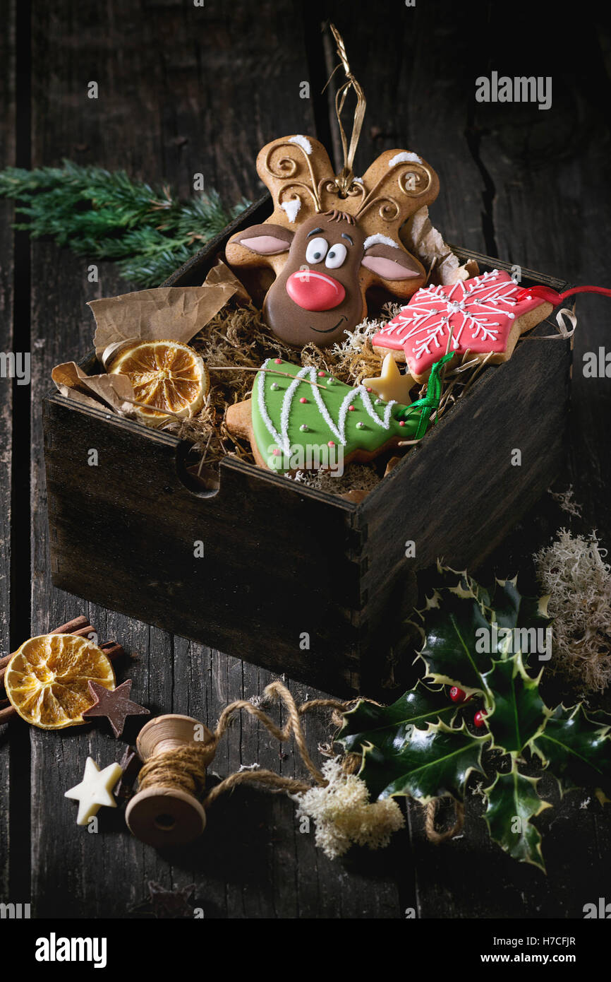 Christmas Handmade patterned gingerbreads as Christmas tree, reindeer Rudolph and snowflake shapes in wooden box - Stock Image