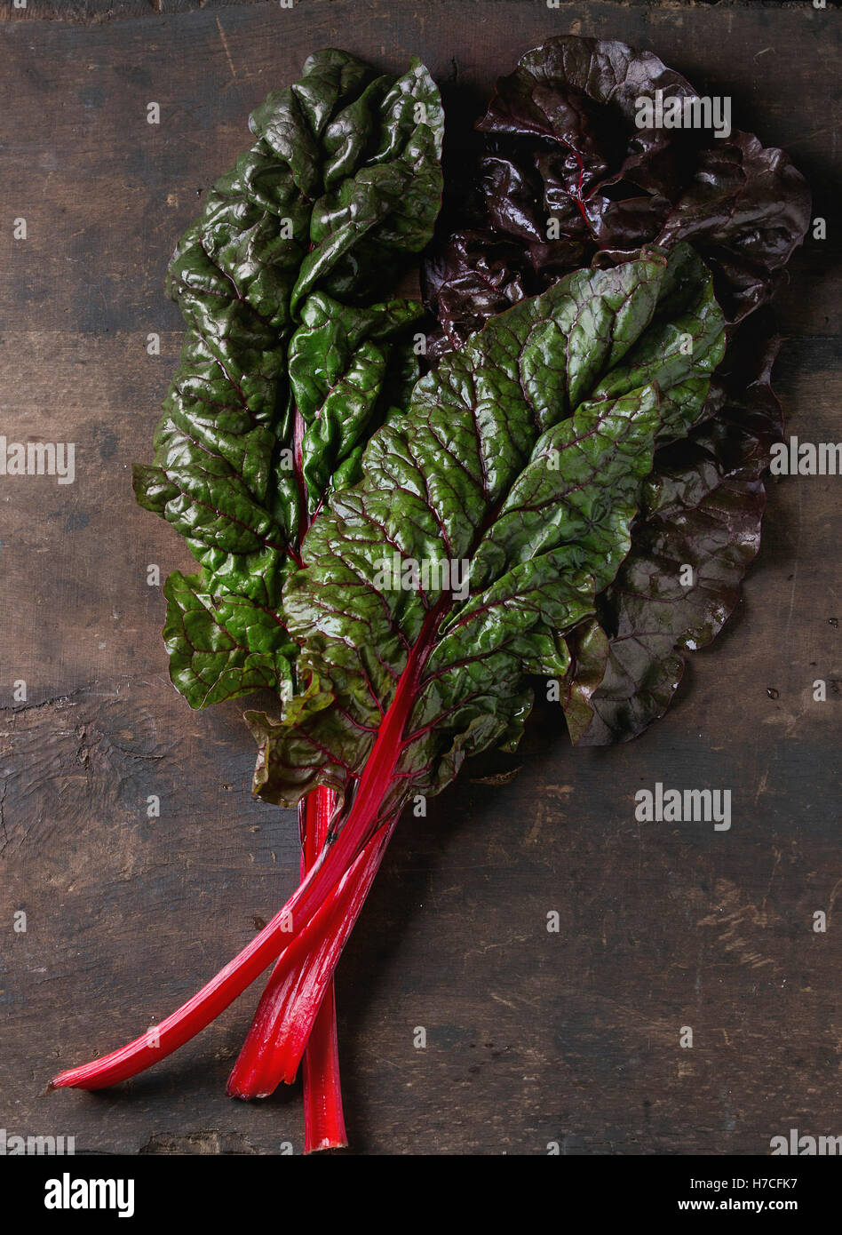 Fresh chard mangold salad leaves over old dark wooden background. Top view with space for text. Healthy eating theme. - Stock Image