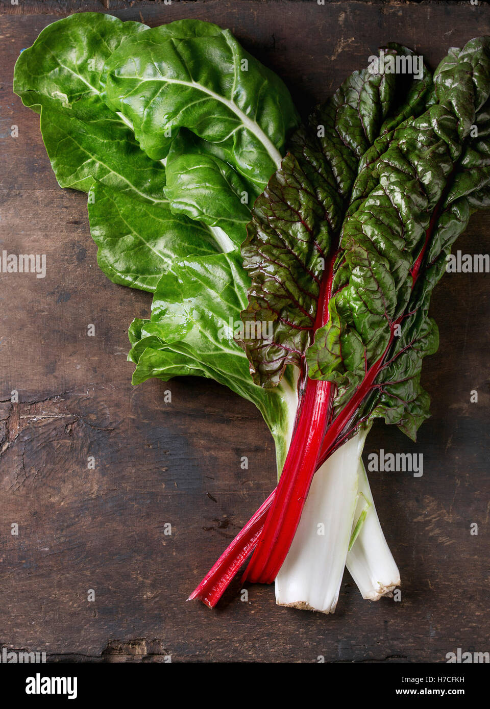 Variety of fresh chard mangold salad leaves over old dark wooden background. Top view with space for text. Healthy - Stock Image