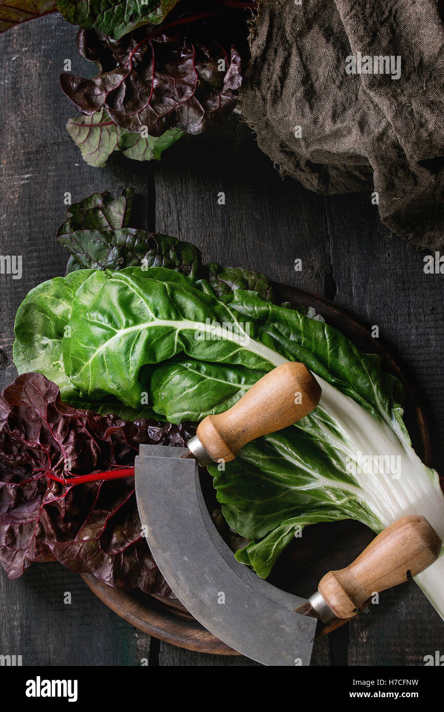 Variety of fresh chard mangold salad leaves on woode chopping board with vintage knife and sackcloth rag over old - Stock Image