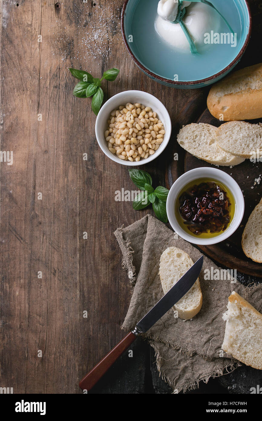 Turquoise bowl whole tied Italian cheese burrata in brine served with pine nuts, sliced bread, basil and dried tomatoes - Stock Image