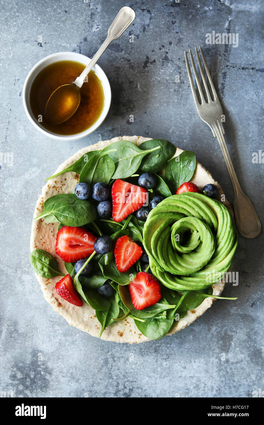 Mixed salad with spinach,berries and avocado rose with honey mustard dressing.Top view - Stock Image