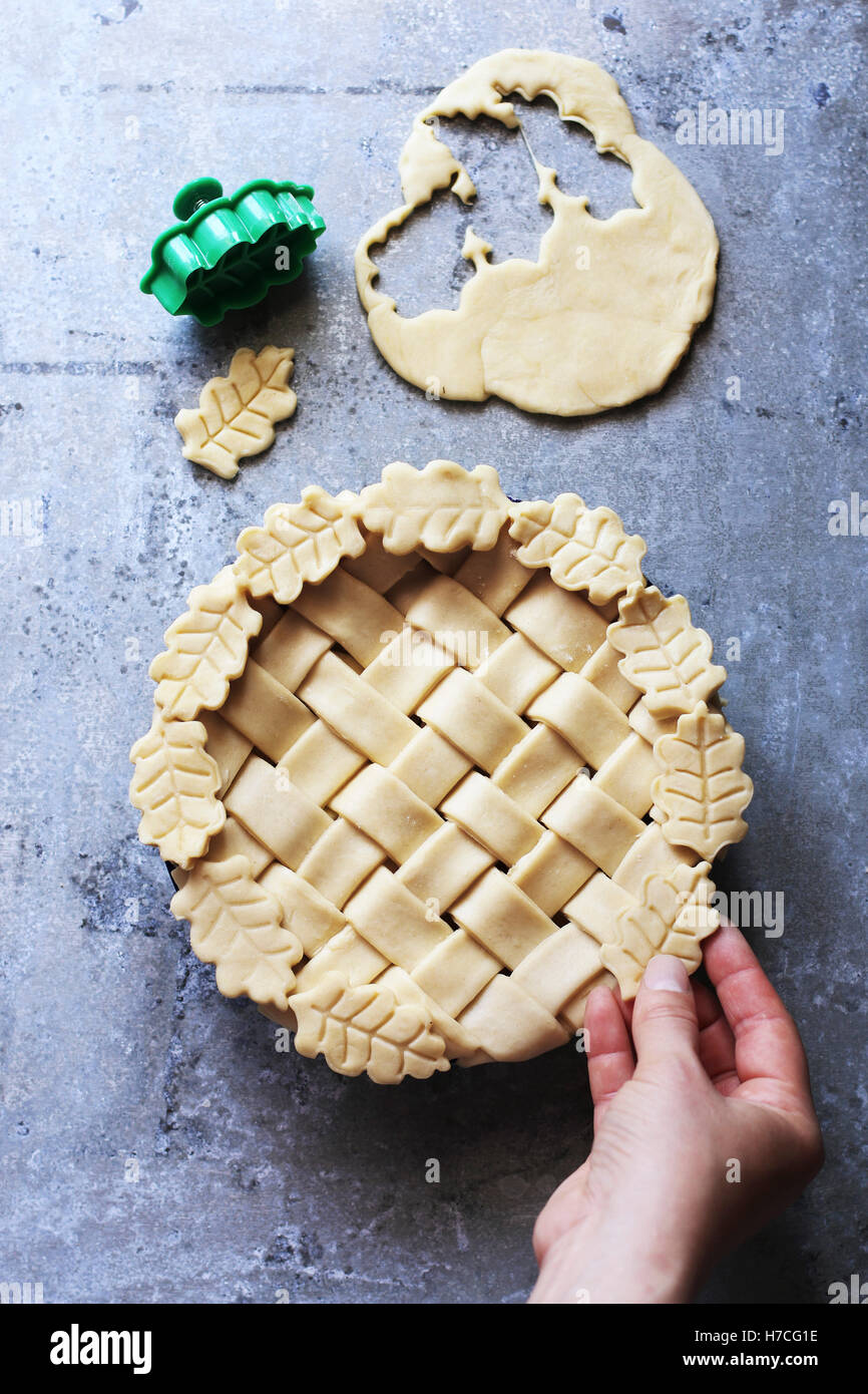 Female hand decorating a pie with leaves .Top view. - Stock Image