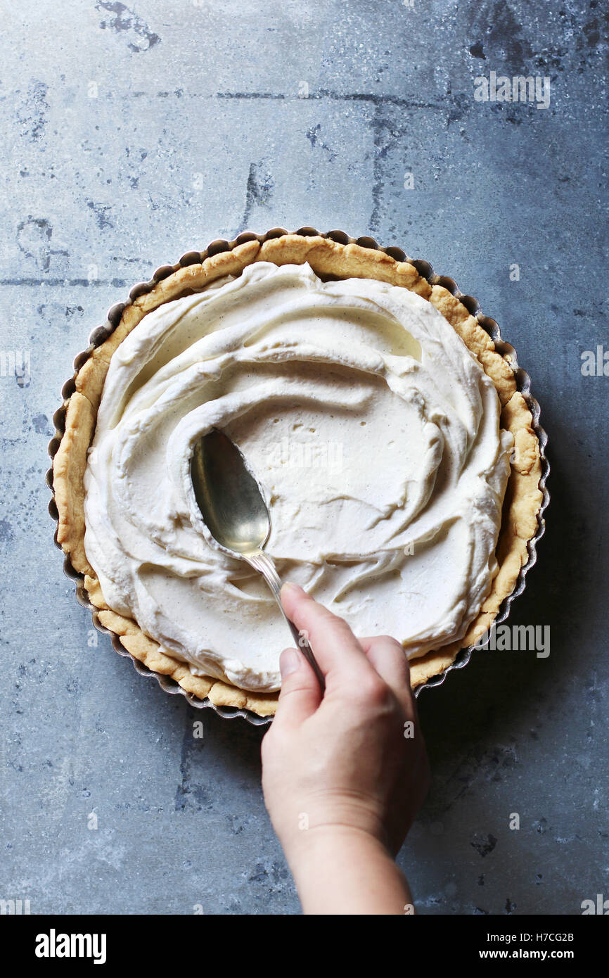Hand spreading with the back of a spoon the whipped cream filling over the bottom of a tart.Top view - Stock Image