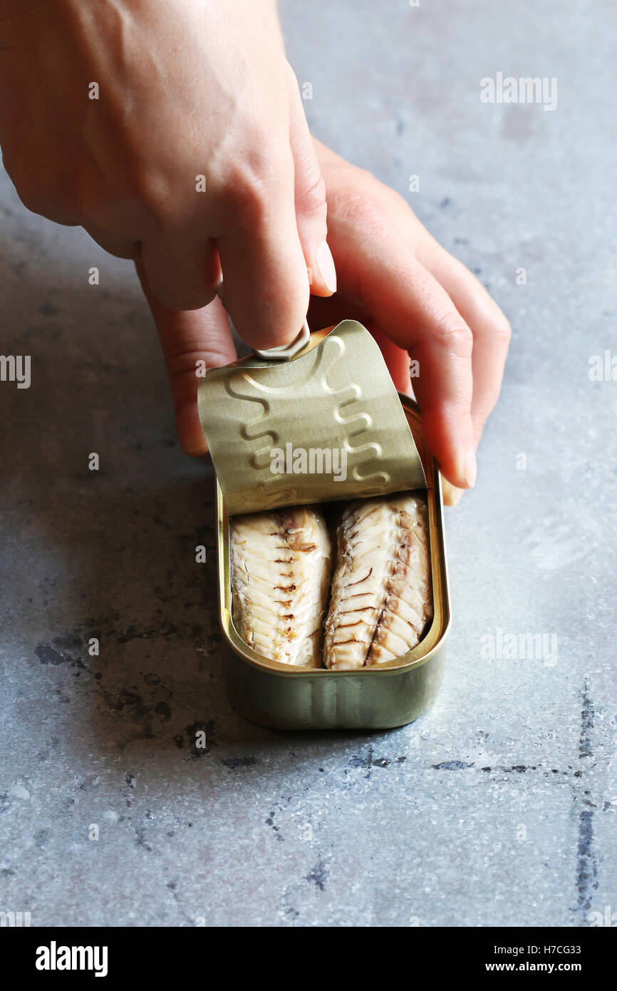 Female hand opening a can with mackerel fillet - Stock Image