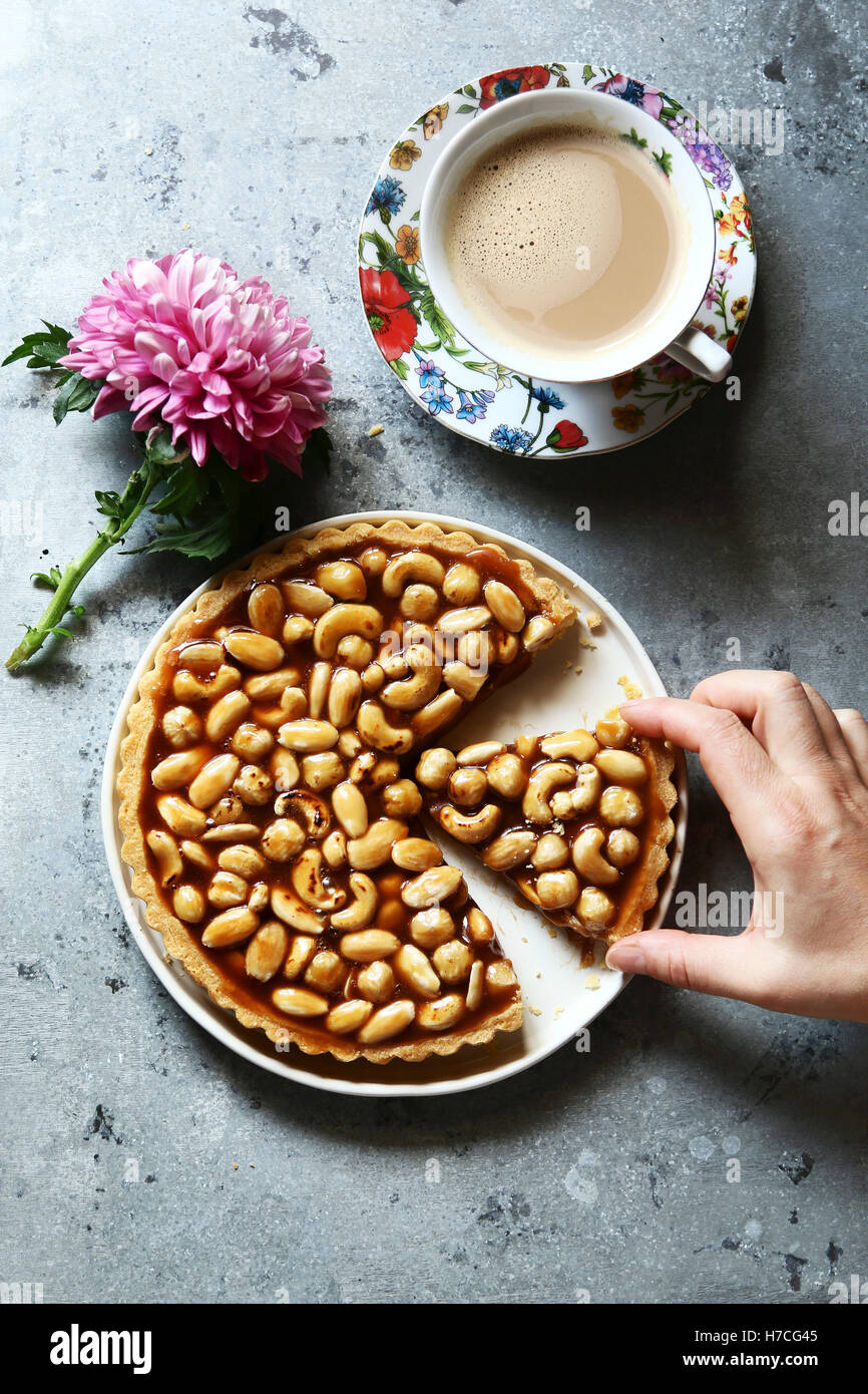 Female hand serving a slice of caramel nut tart with a cup of coffee - Stock Image