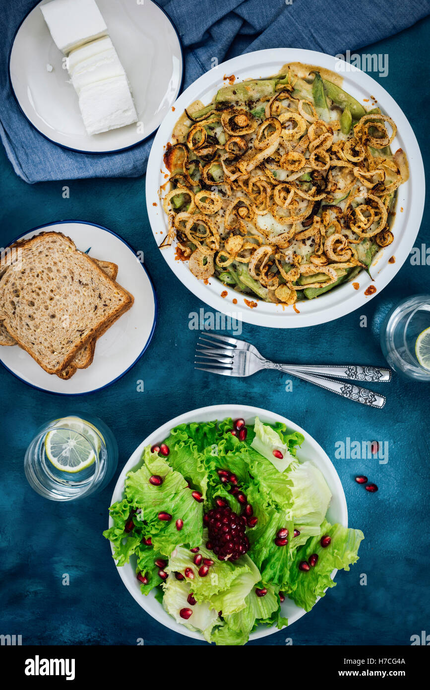 Skinny green bean casserole with mushroom served with a bowl of salad, bread and cheese. - Stock Image