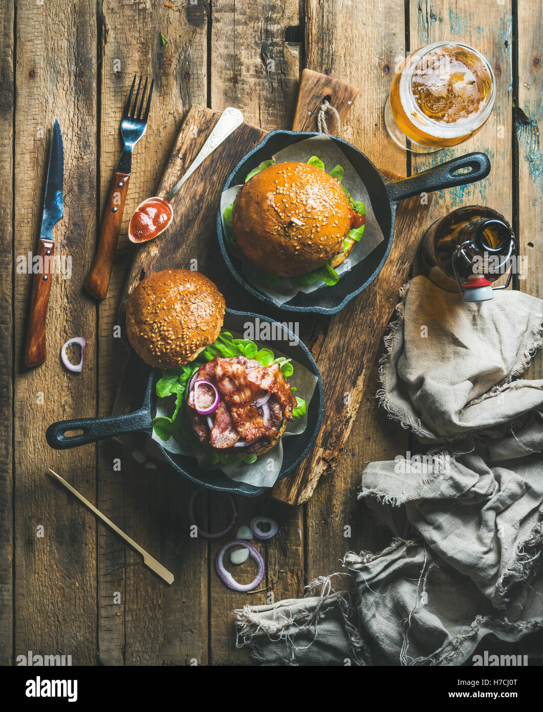 Beef burgers in cast iron pans and glass of beer - Stock Image