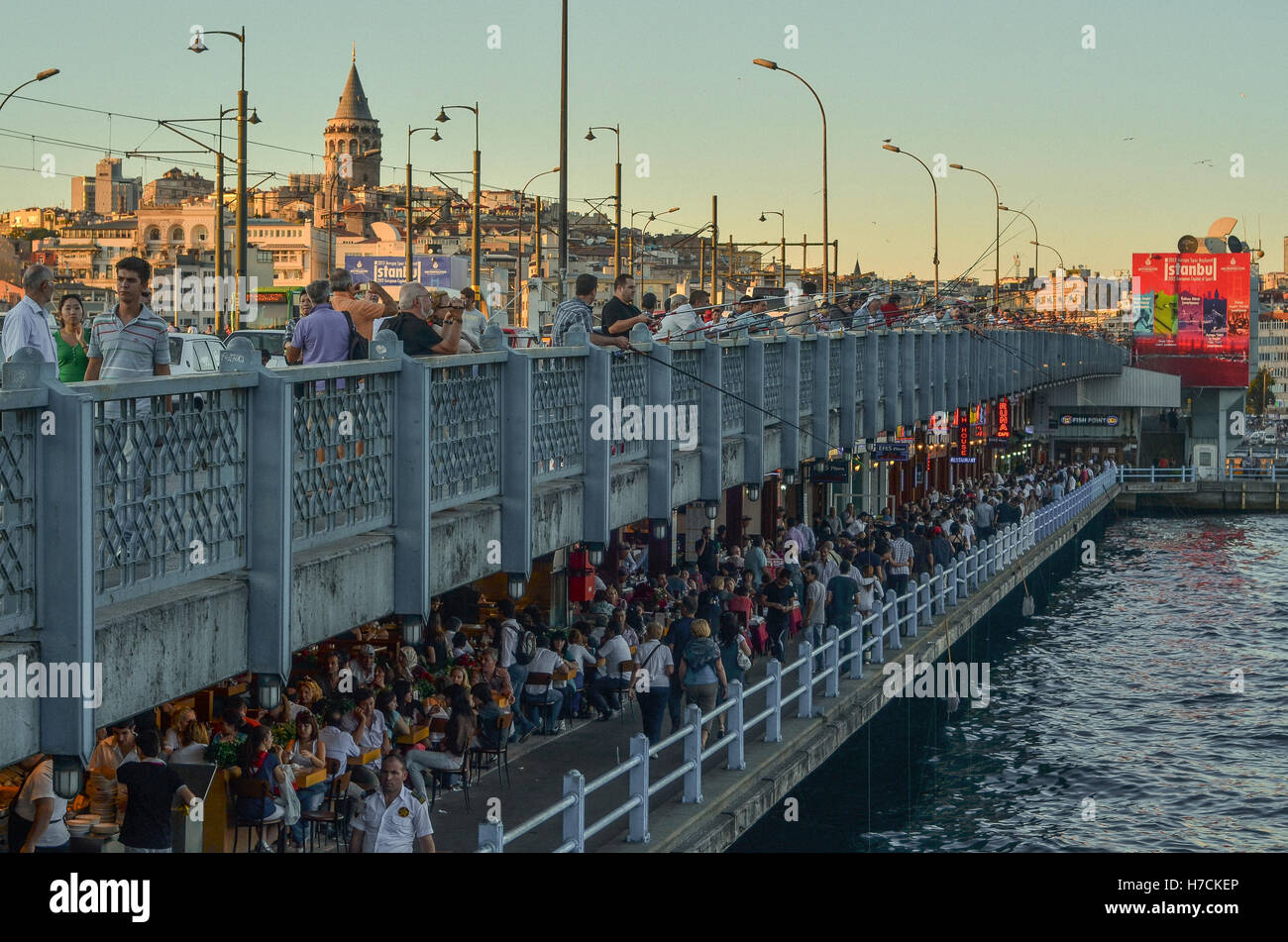 Galata bridge, that links the two banks of the Golden Horn in Istanbul.  Galata Tower can be seen dominating the - Stock Image