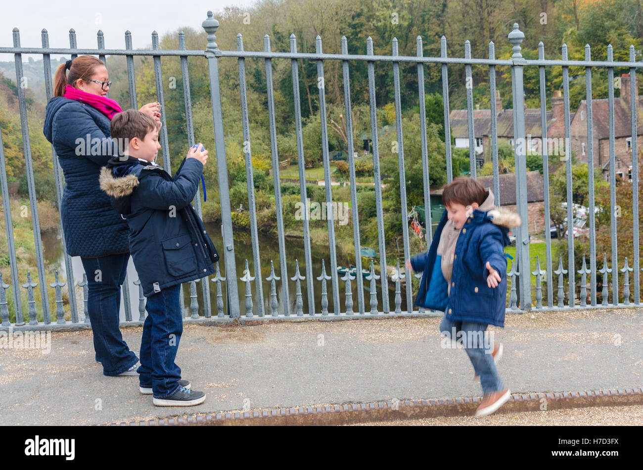 A mum takes a photo of her son doing a star jump while out on a family outing. - Stock Image