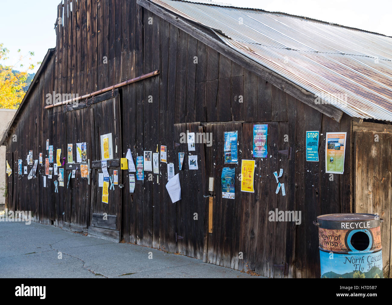 Paper ads posted on an old barn in small town Twisp, Washington, USA. - Stock Image