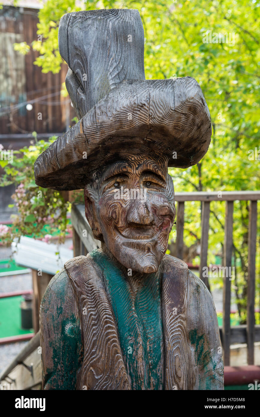 An old wood carved statue of prospector in small western town Winthrop, Washington State, USA. - Stock Image