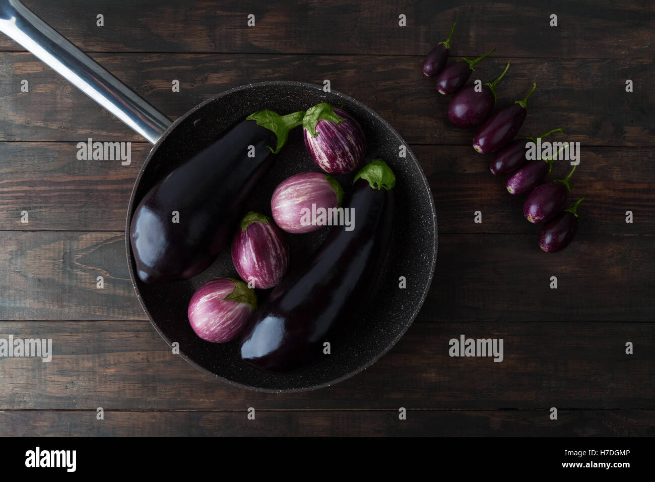 Eggplant varieties arranged on frying pan and wooden table. Top view. - Stock Image