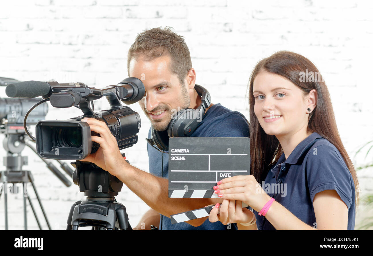 a cameraman and a young woman with a movie camera and clapper - Stock Image