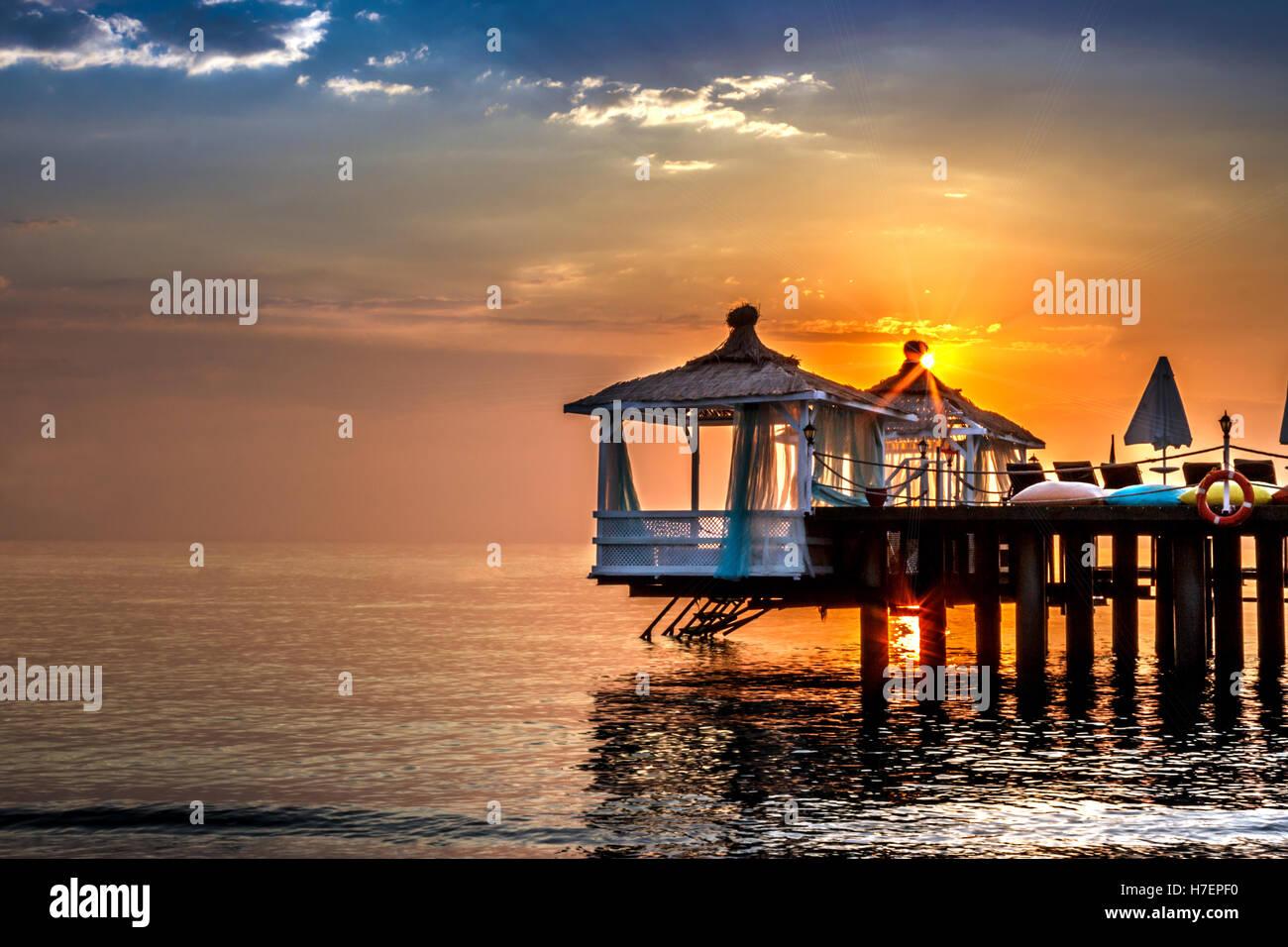 beautiful sunrise over water bungalows - Stock Image