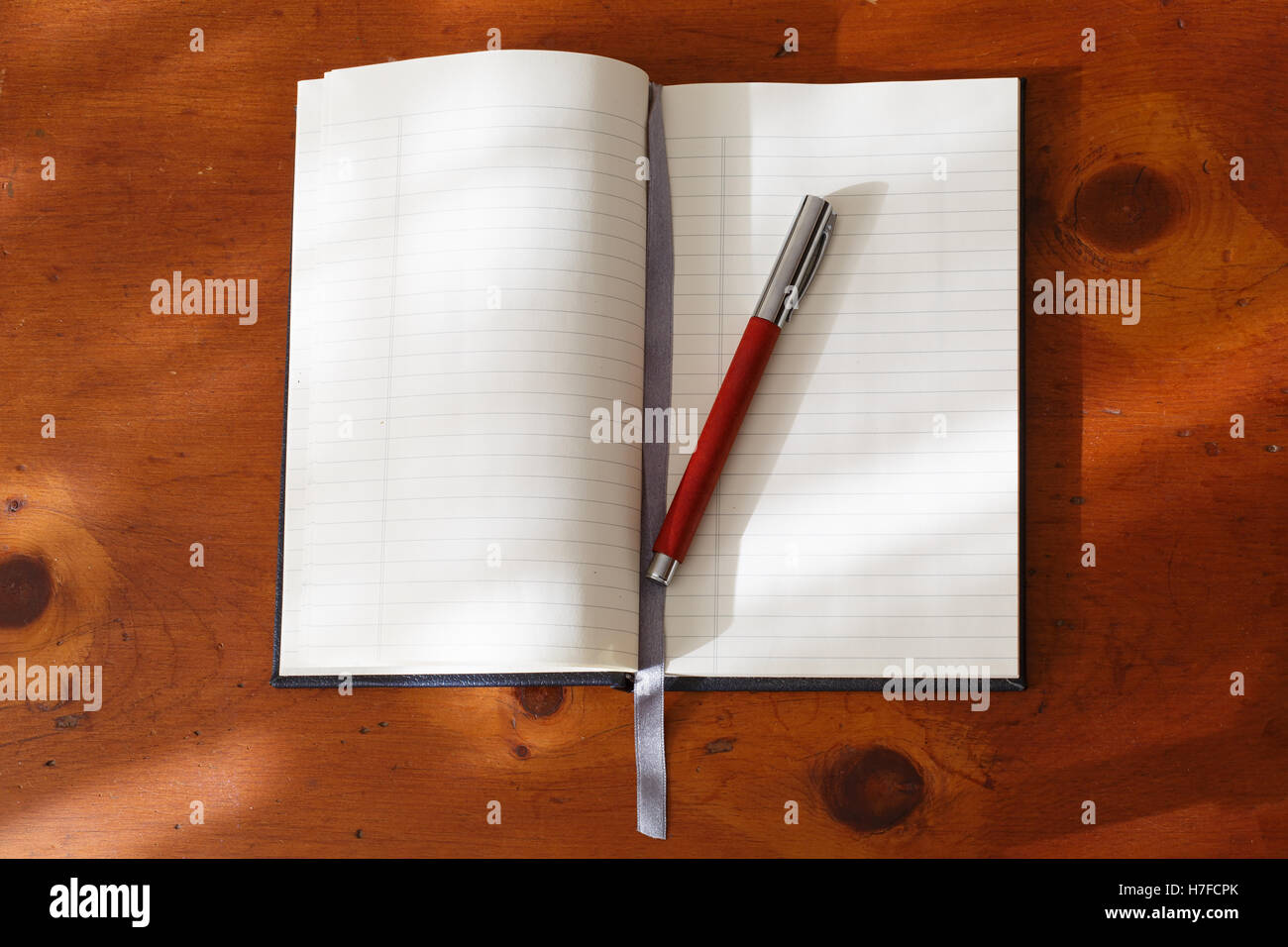 Open blank journal with fountain pen on a wooden desk. - Stock Image