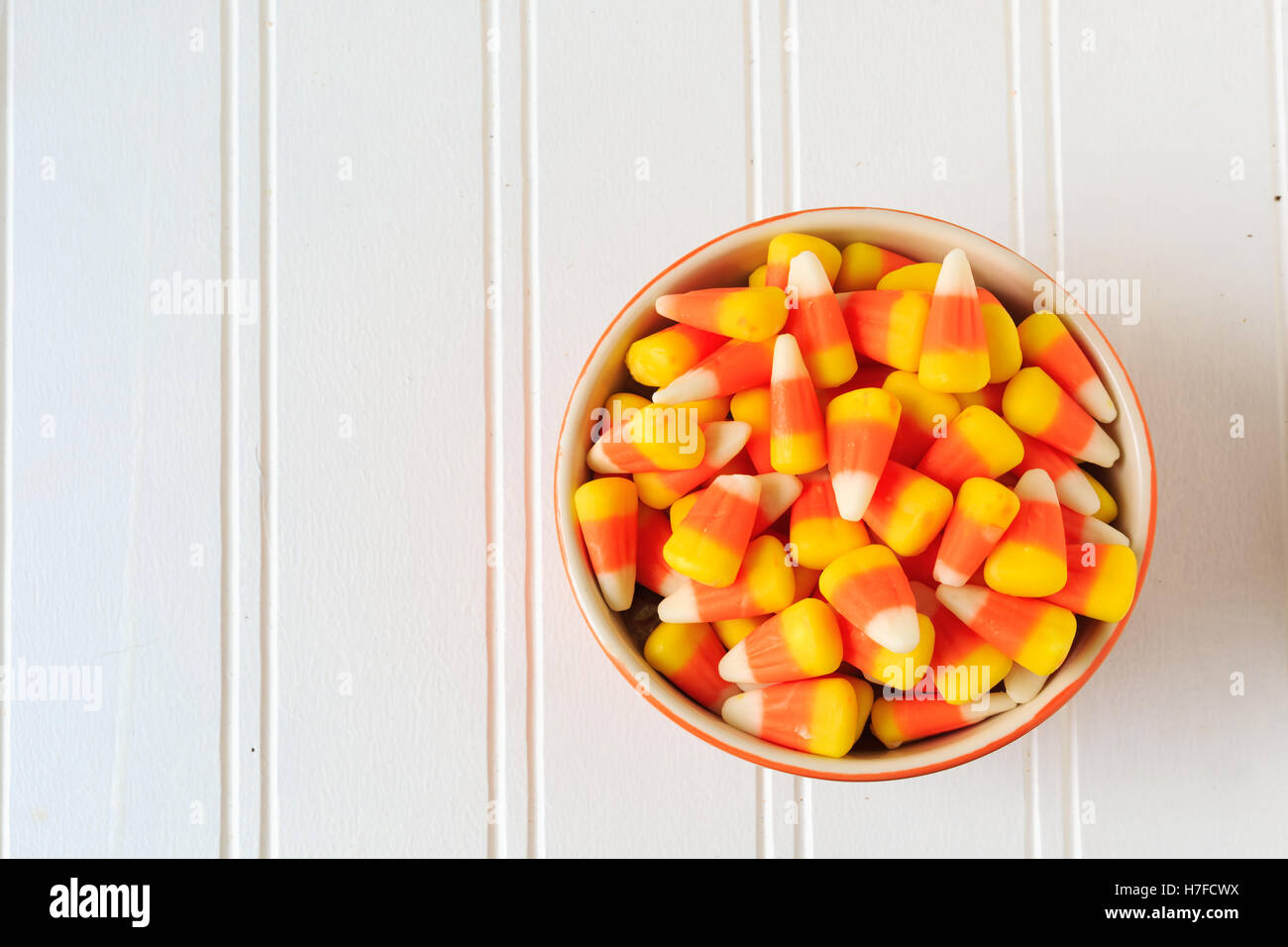 A bowl of candy corn on a wooden table. - Stock Image