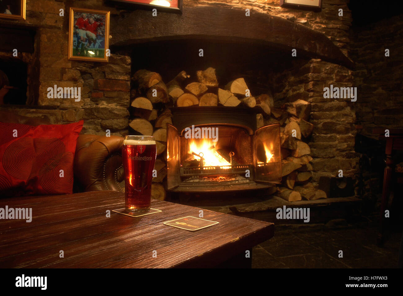 A pint of beer in a cosy pub with a log burner in the UK. - Stock Image