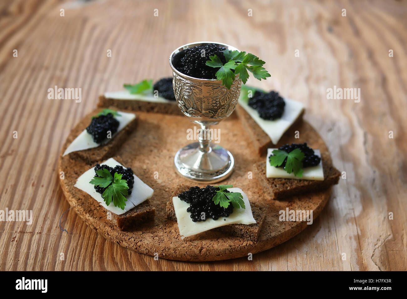 snack black caviar on a wooden background - Stock Image
