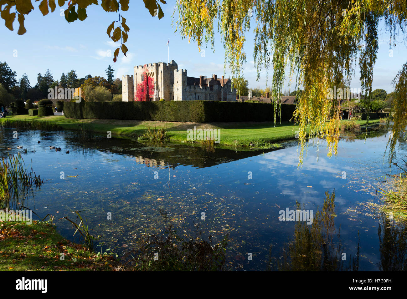Hever Castle & moat, former home of Anne Boleyn, clad with red autumnal virginia creeper & blue sky / sunny - Stock Image