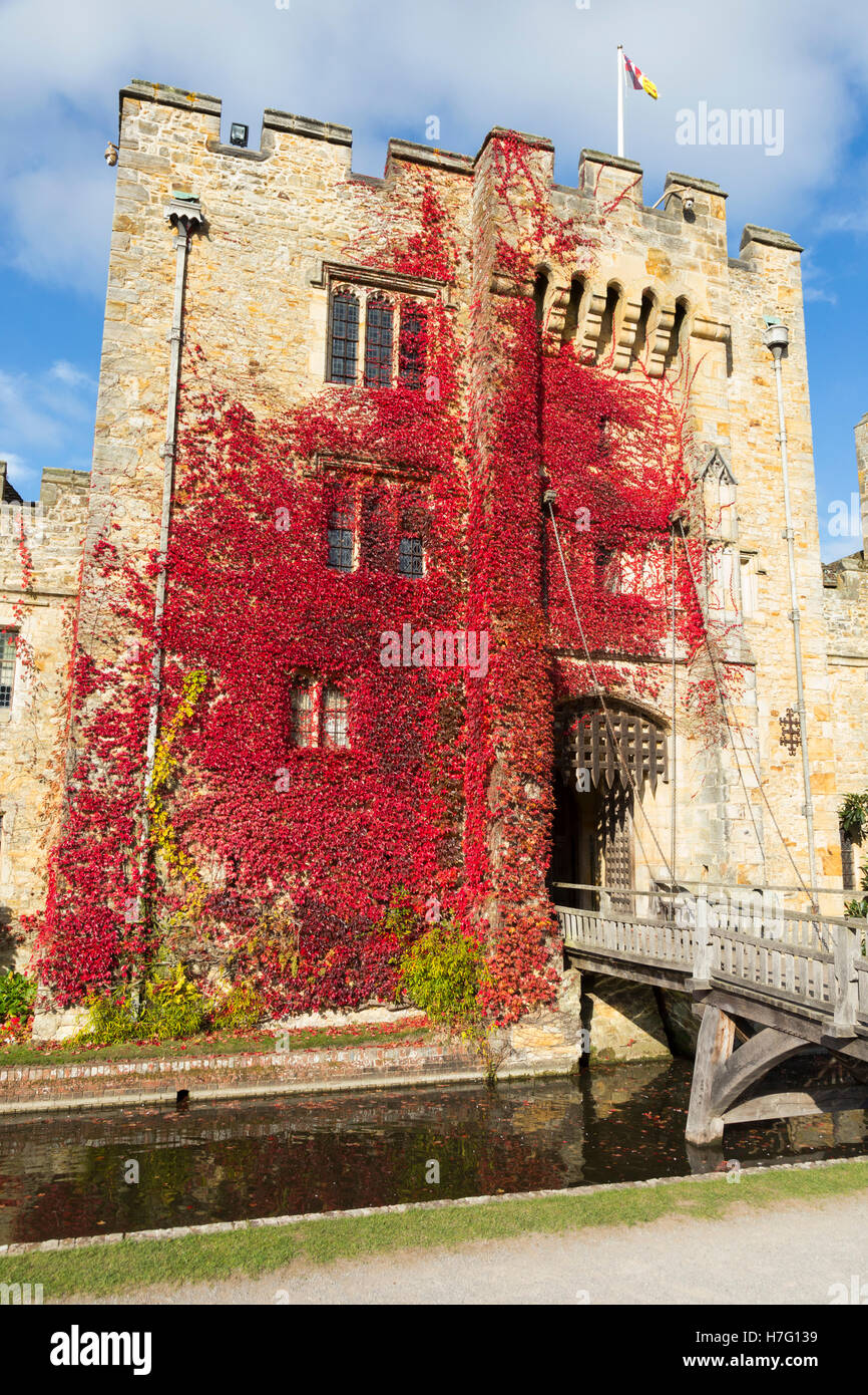 Hever Castle clad with red autumnal virginia creeper: Blue sky / sunny skies / sun & drawbridge / draw bridge - Stock Image