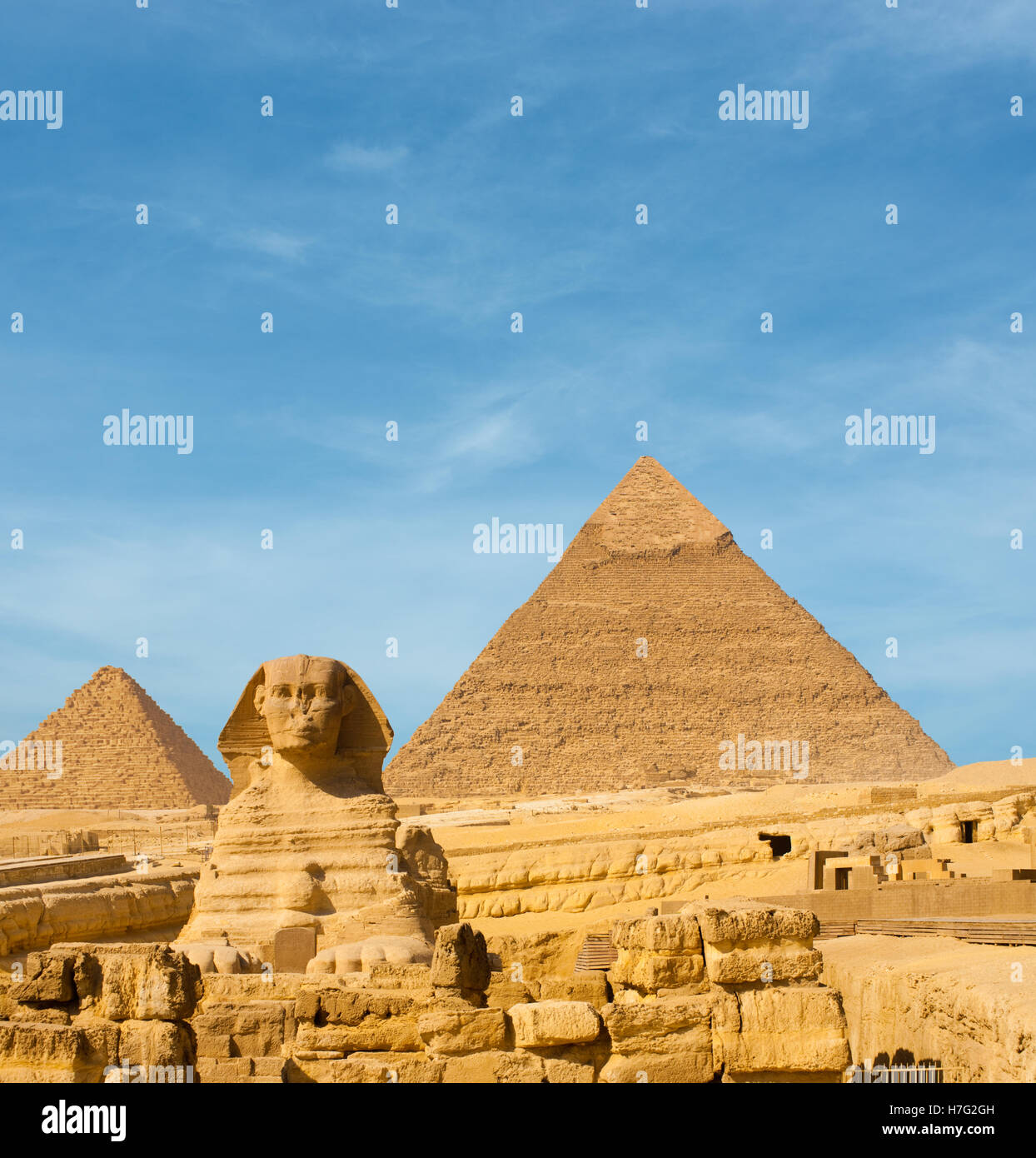 Front facing Sphinx and the large Egyptian Pyramids of Khafre, Menkaure slightly offset in front of blue sky in - Stock Image