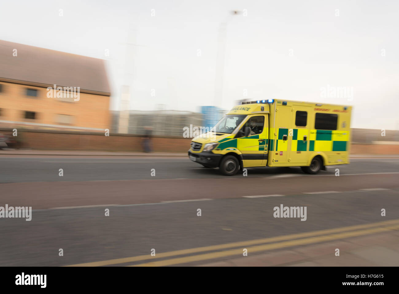 An ambulance driving fast on an emergency call  with motion blur in Cambridge UK - Stock Image