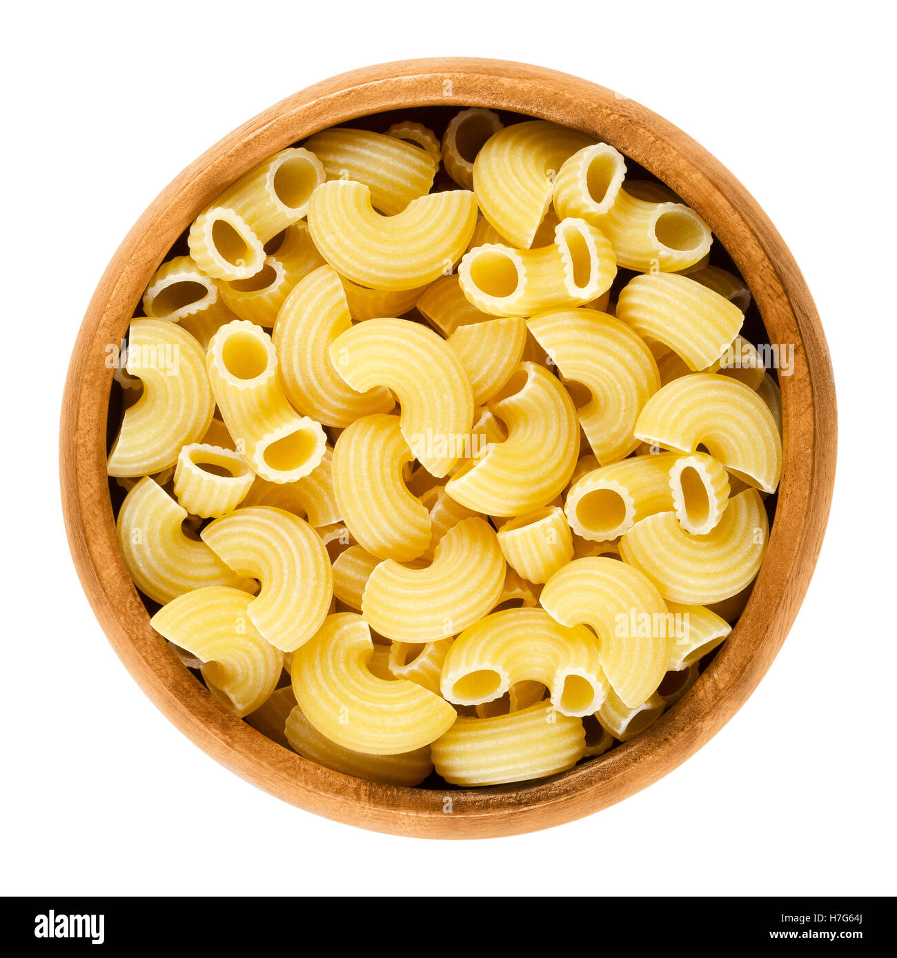 Chifferi pasta in wooden bowl. Bent tubes, short-cut and wide macaroni. Italian noodles prepared with eggs. - Stock Image