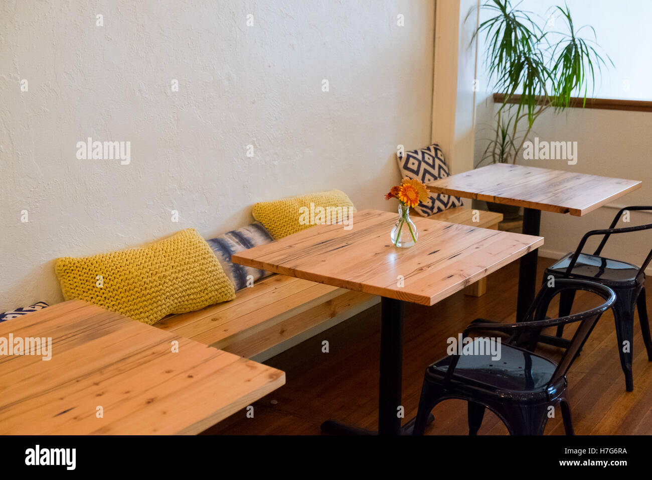 Bench seating at a coffee shop restaurant with small cafe tables and